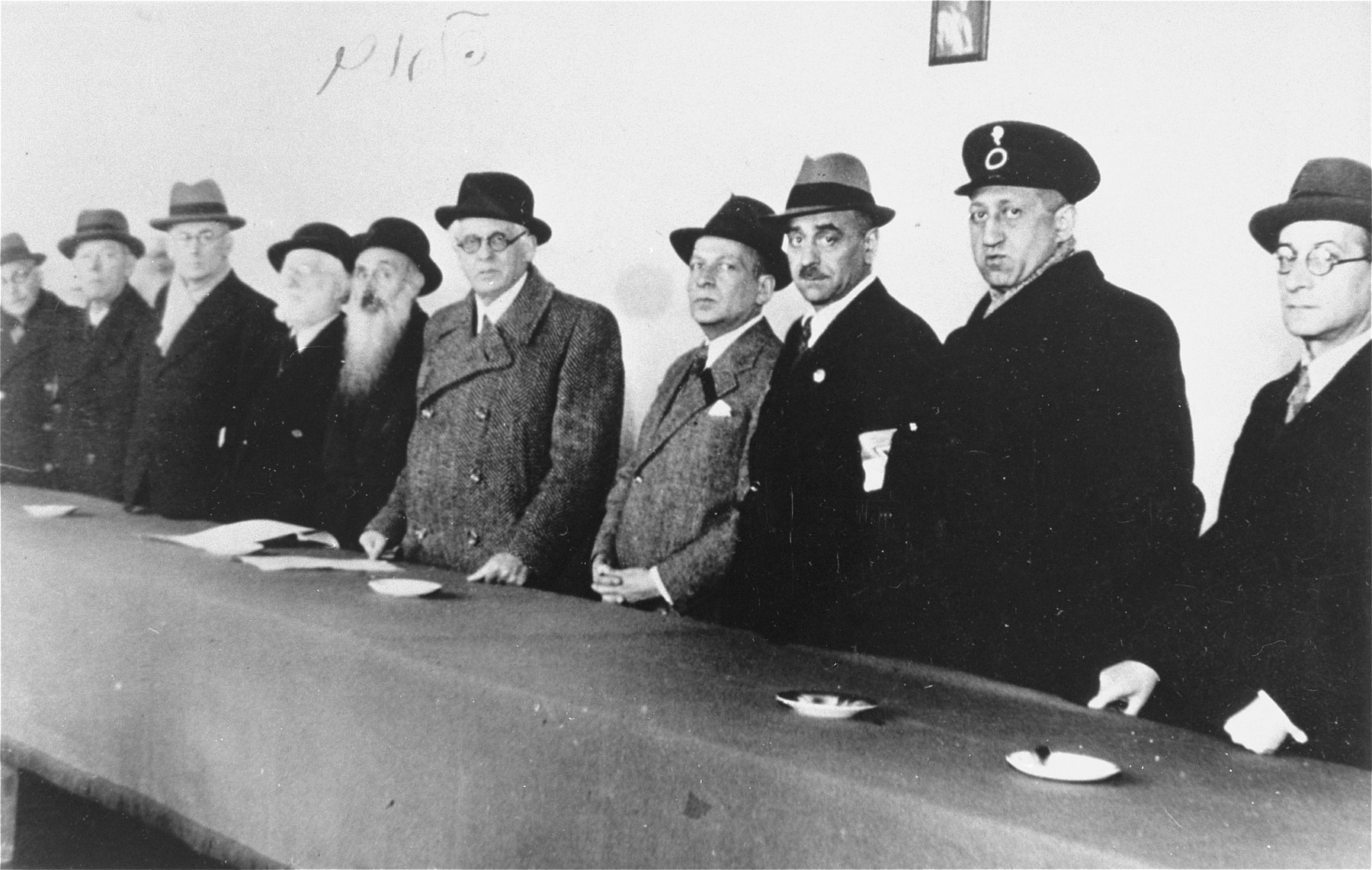 Members of the Lodz ghetto Jewish council stand behind a long table.  Among those pictured are Mordechai Chaim Rumkowski (fifth from the right), Rabbi Yosif Fajner (sixth from the right), Leon Rozenblat (third from the right), Dr. Leon Szykier (second from the right) and Max Szczesliwy.