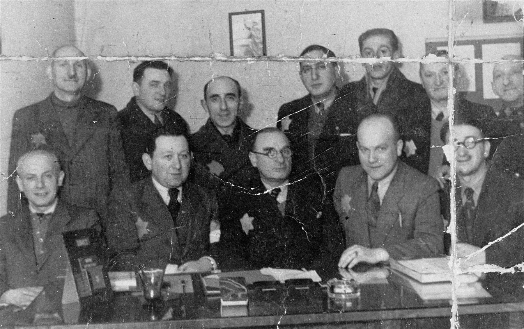 Group portrait of members of the Jewish council in an office in the Lodz ghetto.  Among those pictured are Zygmunt Reingold, director of food supply (seated second from the left) and Max Szczesliwy, co-director (seated in the middle).