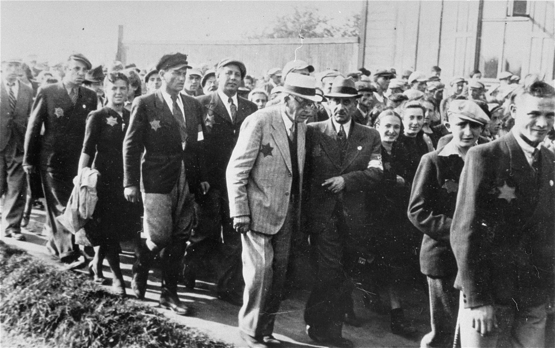 Mordechai Chaim Rumkowski, chairman of the Jewish Council (center), leaves the site of a public demonstration in the Lodz ghetto after delivering a speech to calm the people's fear and anger about food provisioning in the ghetto.    Also pictured are: Leon Rozenblat (walking with Rumkowski) and Shmuel Eizmann (Rumkowksi's bodyguard, behind Rumkowski and to the right).