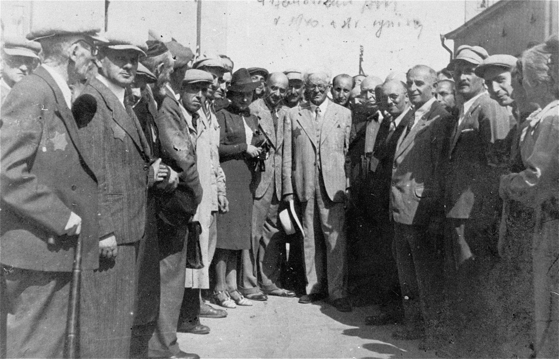Jewish council chairman Mordechai Chaim Rumkowski (center) stands among a crowd of people who have gathered outside in the Lodz ghetto.  Also pictured are Leon Rozenblat (center, left) and Dora Fuks (next to Rozenblat).