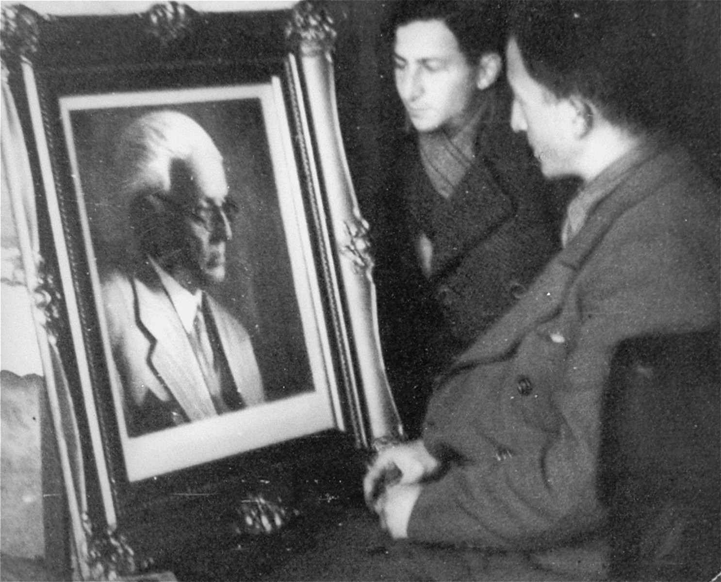 Nachman Zonabend (center) and Mendel Grosman (right) examine a framed portrait of Jewish Council chairman Mordechai Chaim Rumkowski.    The portrait was photographed by Mendel Grosman and had to be displayed in every office in the Lodz ghetto. The original framed portrait was given to Rumkowski.