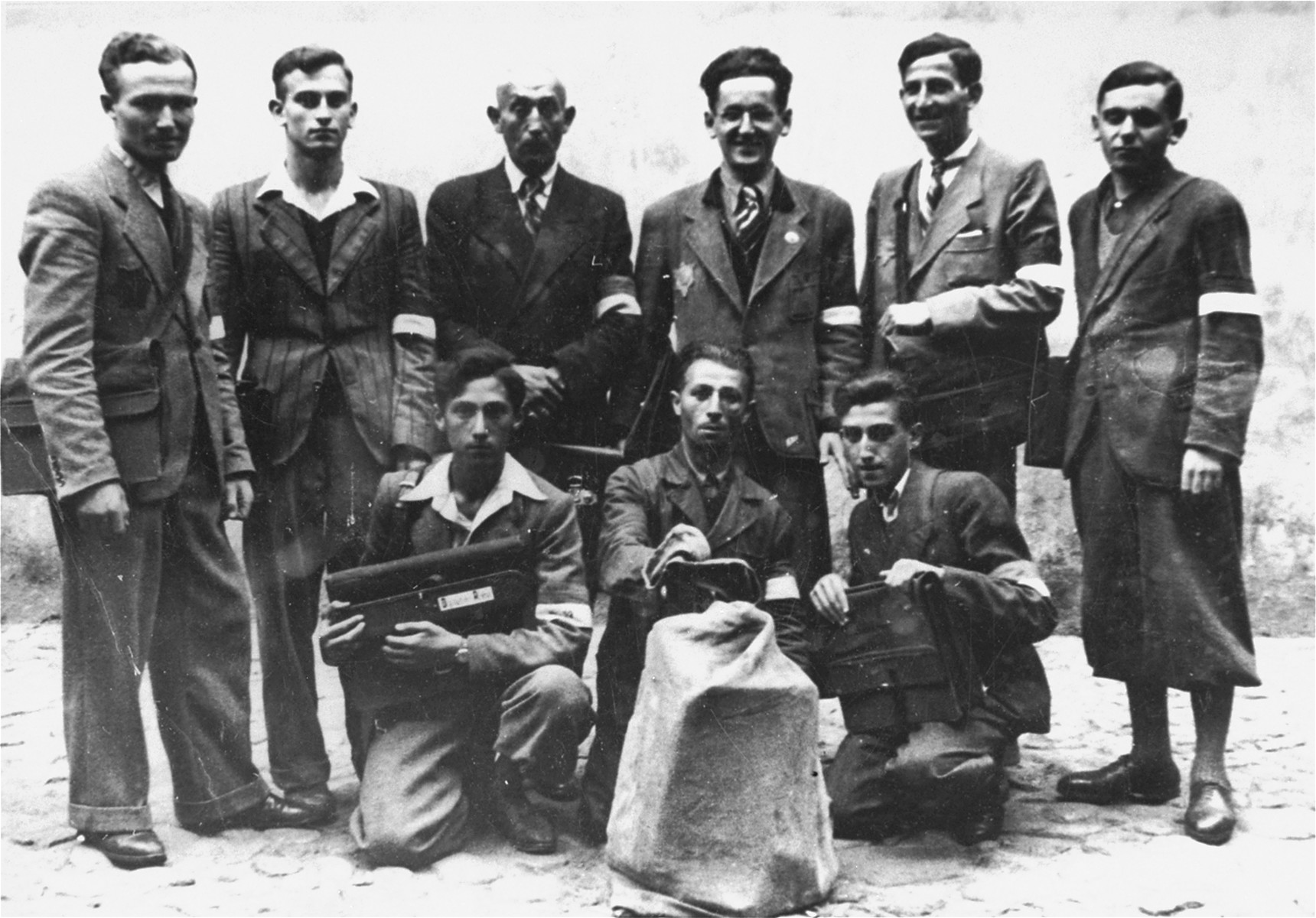 Group portrait of employees in the Lodz ghetto post office.    Among those pictured is Nachman Zonabend (standing second from the right).