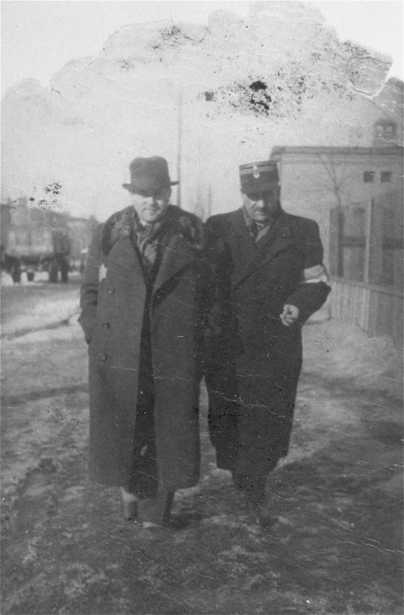 Leon Rozenblat, chief of the Lodz ghetto police (right), walks along a street in the ghetto with an unidentified man.  The other man may be Stanislaw Jacobson, Chief Ghetto judge.