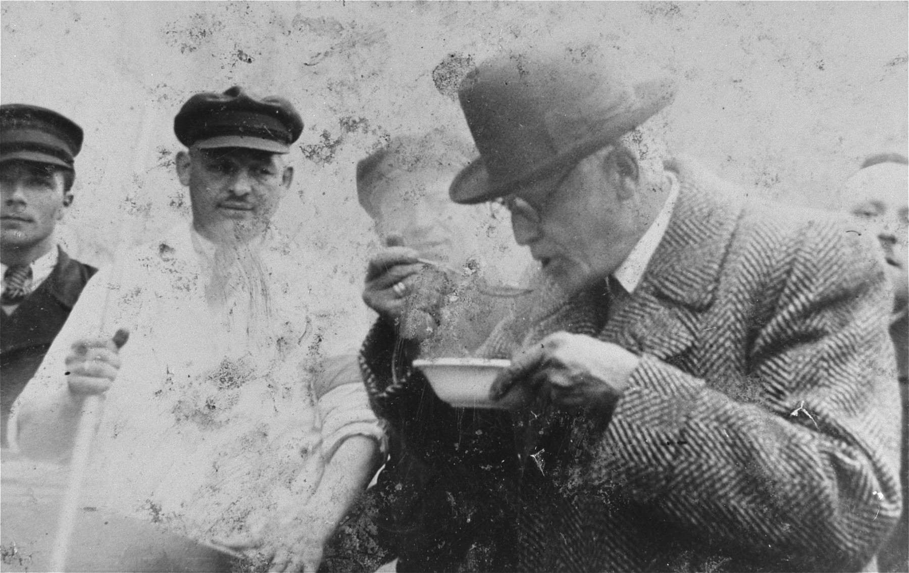 Jewish council chairman Mordechai Chaim Rumkowski, eats a bowl of soup [probably at a newly opened soup kitchen] in the Lodz ghetto.