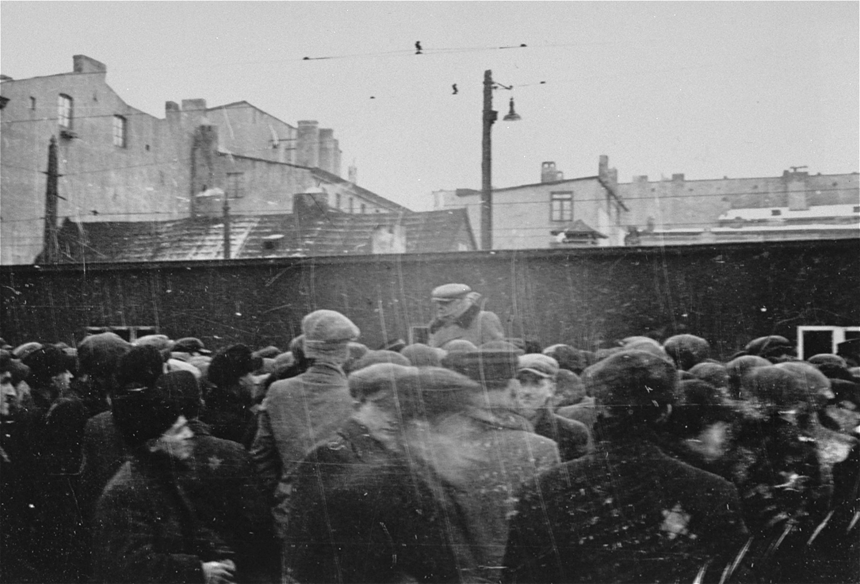 Jewish council chairman Mordechai Chaim Rumkowski speaks to a large crowd at an outdoor meeting in the Lodz ghetto.
