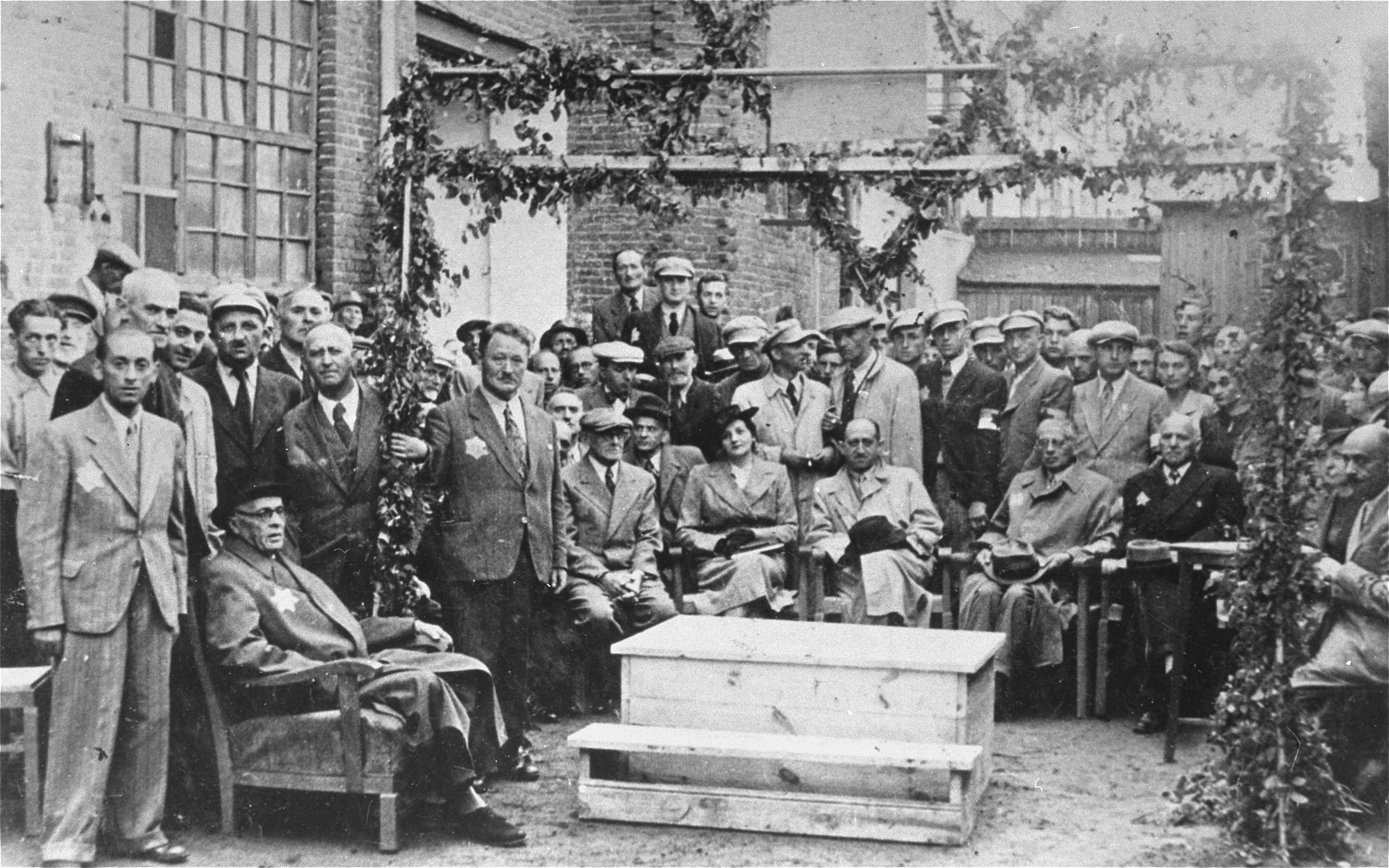 Mordechai Chaim Rumkowski (seated at the left) attends a public ceremony in the Lodz ghetto.  Among those pictured are: Baruch Praszker (standing behind Rumkowski), Stefania Dawidowicz (seated in the center, wearing a hat), Dr. Leon Szykier (seated next to Dawidowicz), Jozef Rumkowski (seated next to Szykier), Leon Rozenblat (far right).  All others are members of the ghetto police.