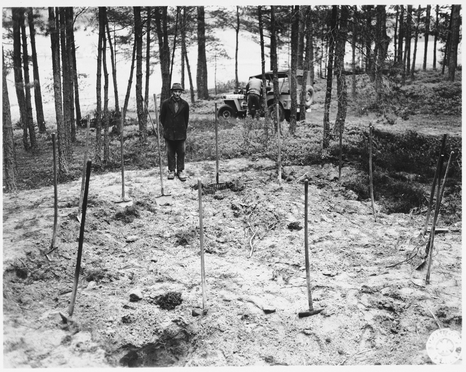 The local Burgomeister views the mass grave in Stamsried, Germany before it is opened for exhumation.  (Photograph taken by the 166th Signal Corps Company.)