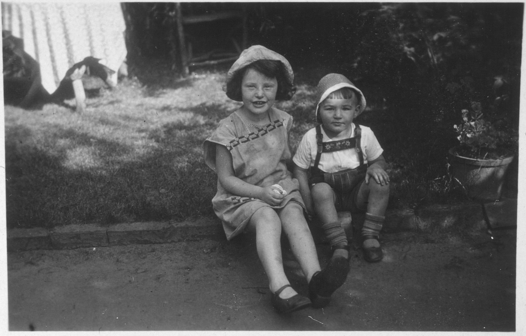 Two young Jewish children sit outside their home in Moenchengladbach, Germany.  Pictured are members of the Hermanns family.