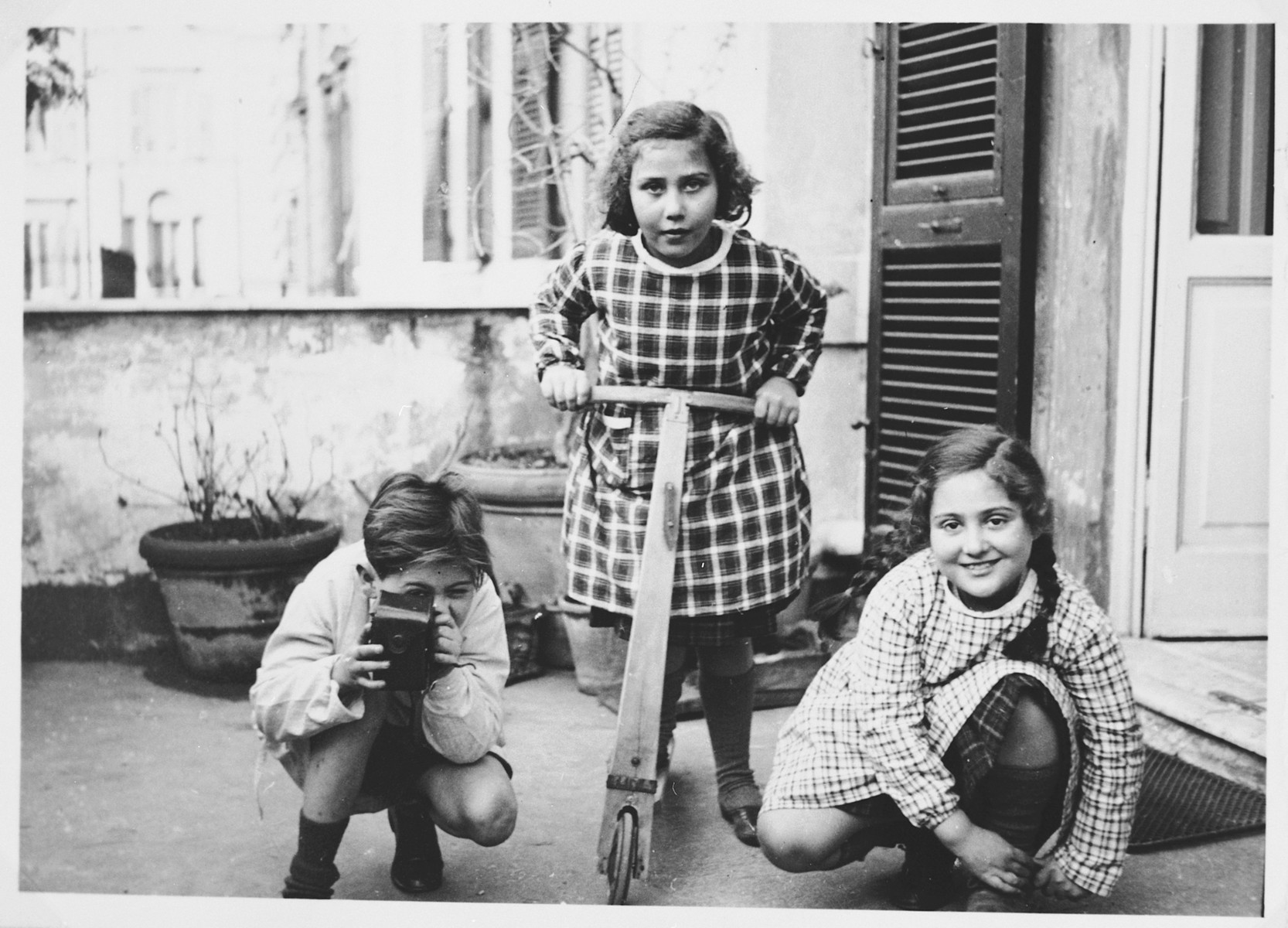 Three Jewish children play in the courtyard of their home.  Pictured are Emanuele Pacifici with his cousins Fausta and Gilda Cassuto.