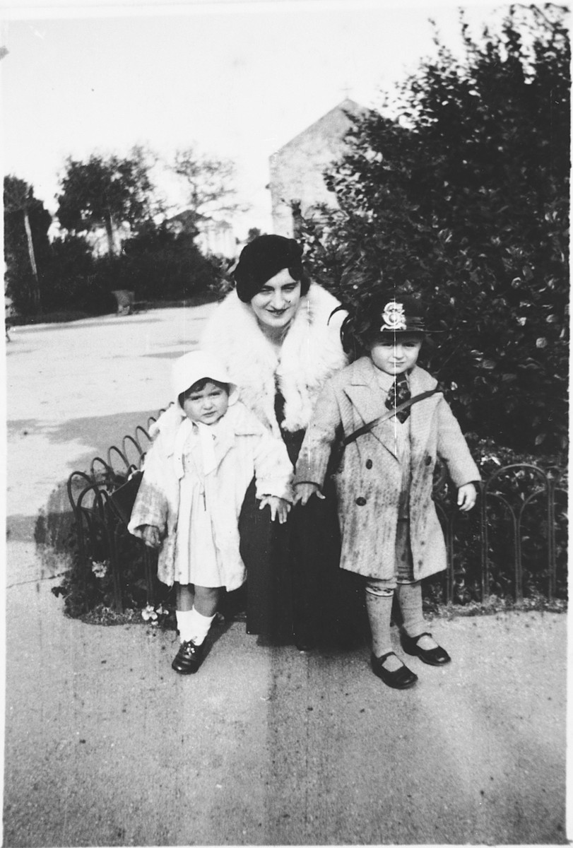 Vanda Pacifici poses with her children Emanuele and Miriam on a street in Rhodes.  The church of San Giovanni is in the background.
