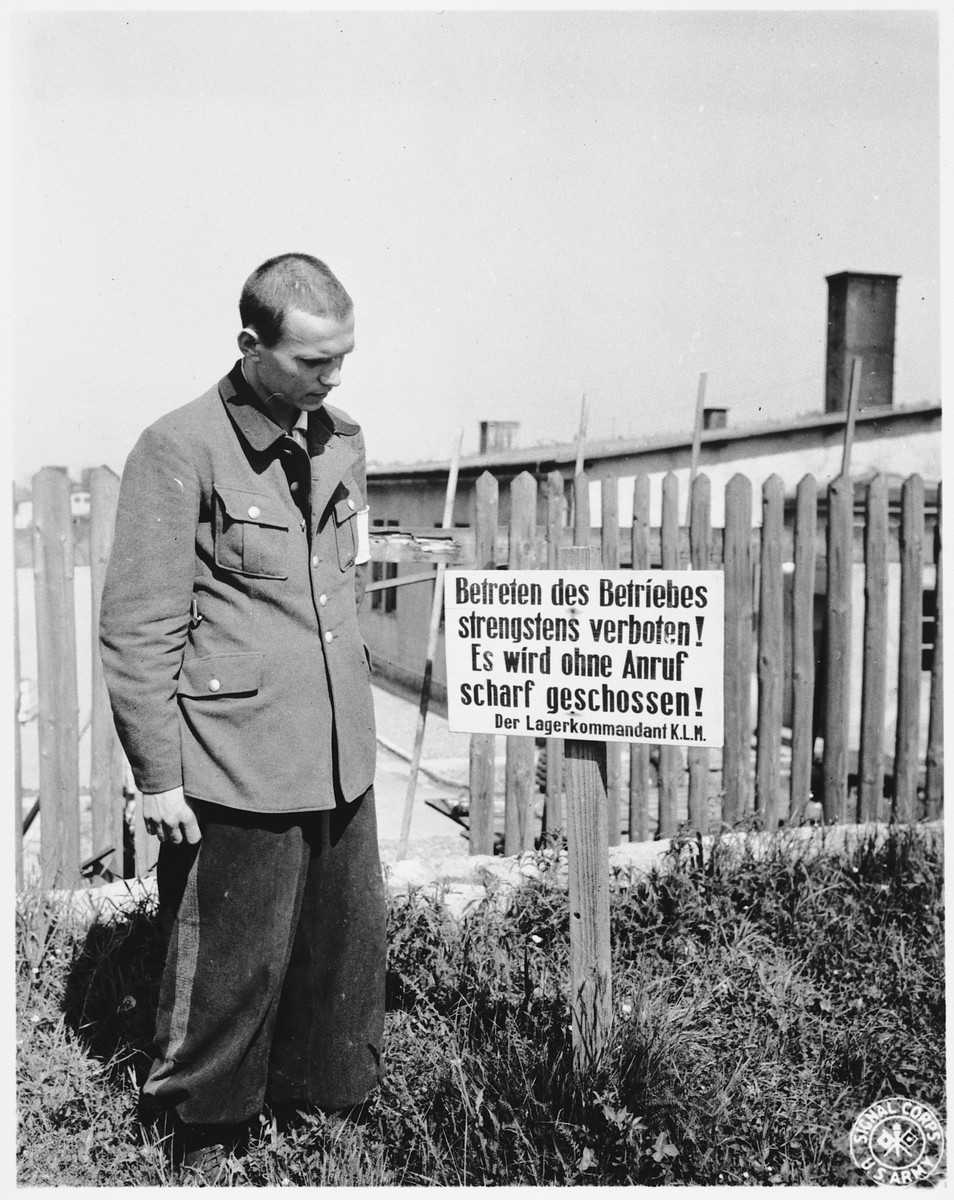 "An unidentified man [perhaps a former POW] poses next to a German sign in the newly liberated Mauthausen concentration camp.  The sign reads: ""Entering this factory is strictly forbidden.  Trespassers will be shot without warning. The camp commandant, K.L.M."""