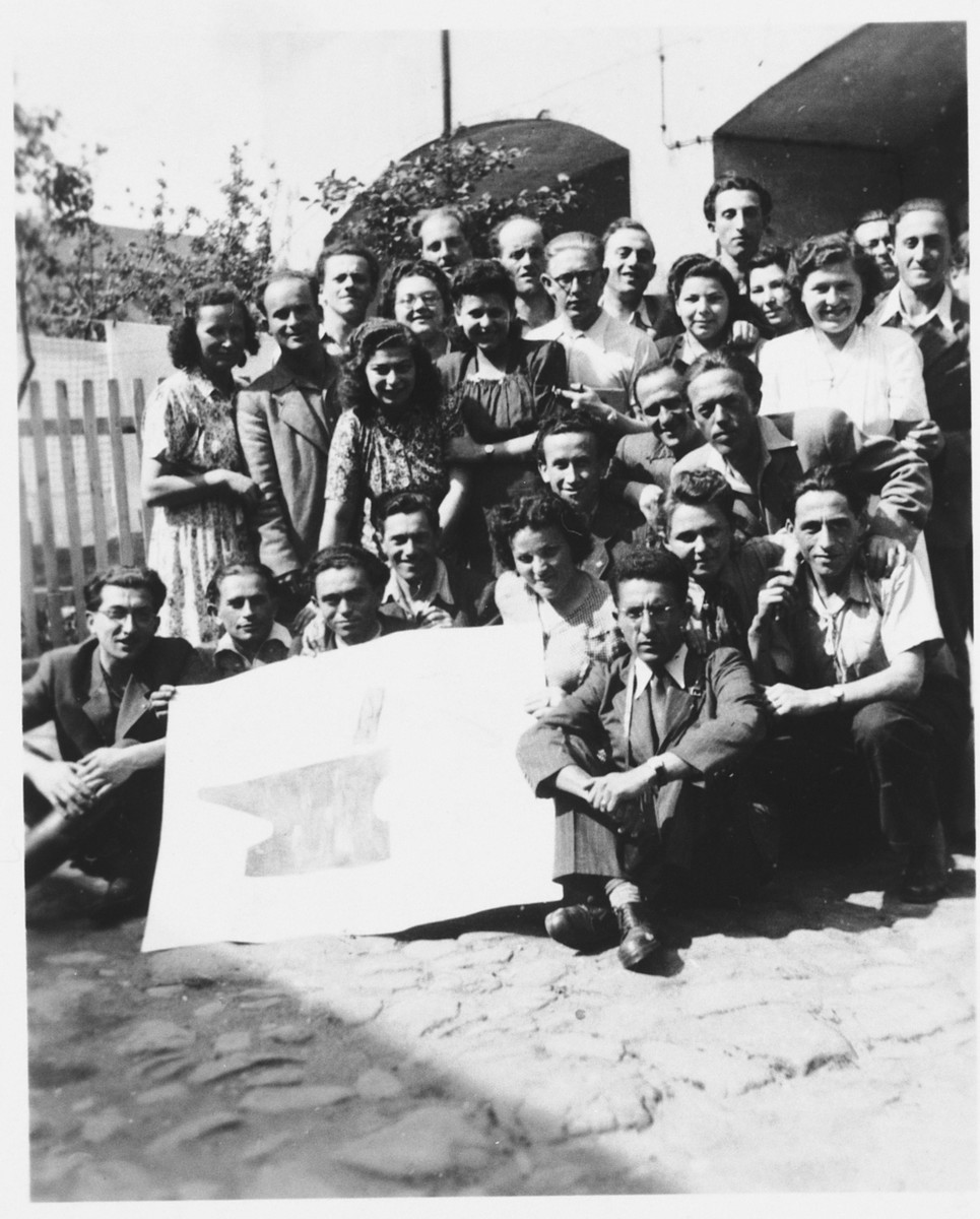 Group portrait of Jewish DPs who are members of the Dror-Hehalutz Zionist youth movement, posing with a sign in Litomerice, Czechoslovakia.
