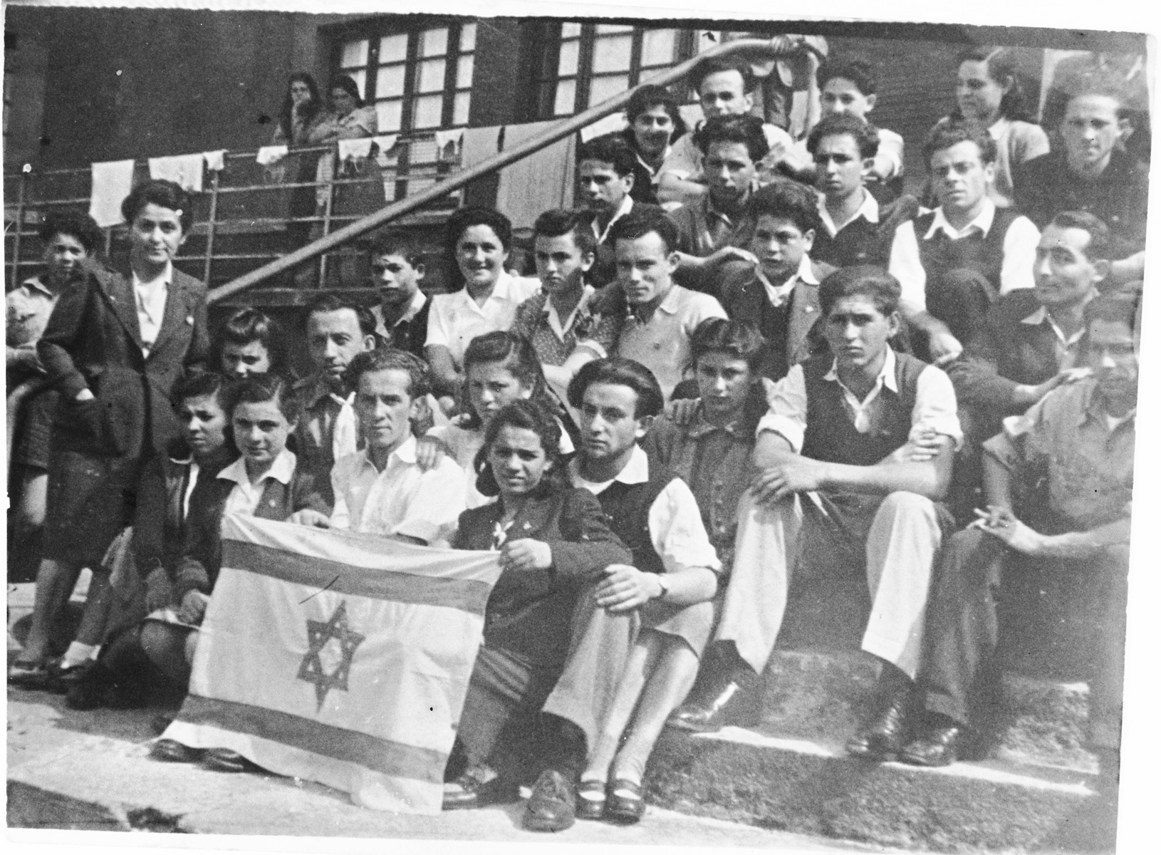 A group of teenagers poses of the steps of the Selvino children's home with an Israeli flag.