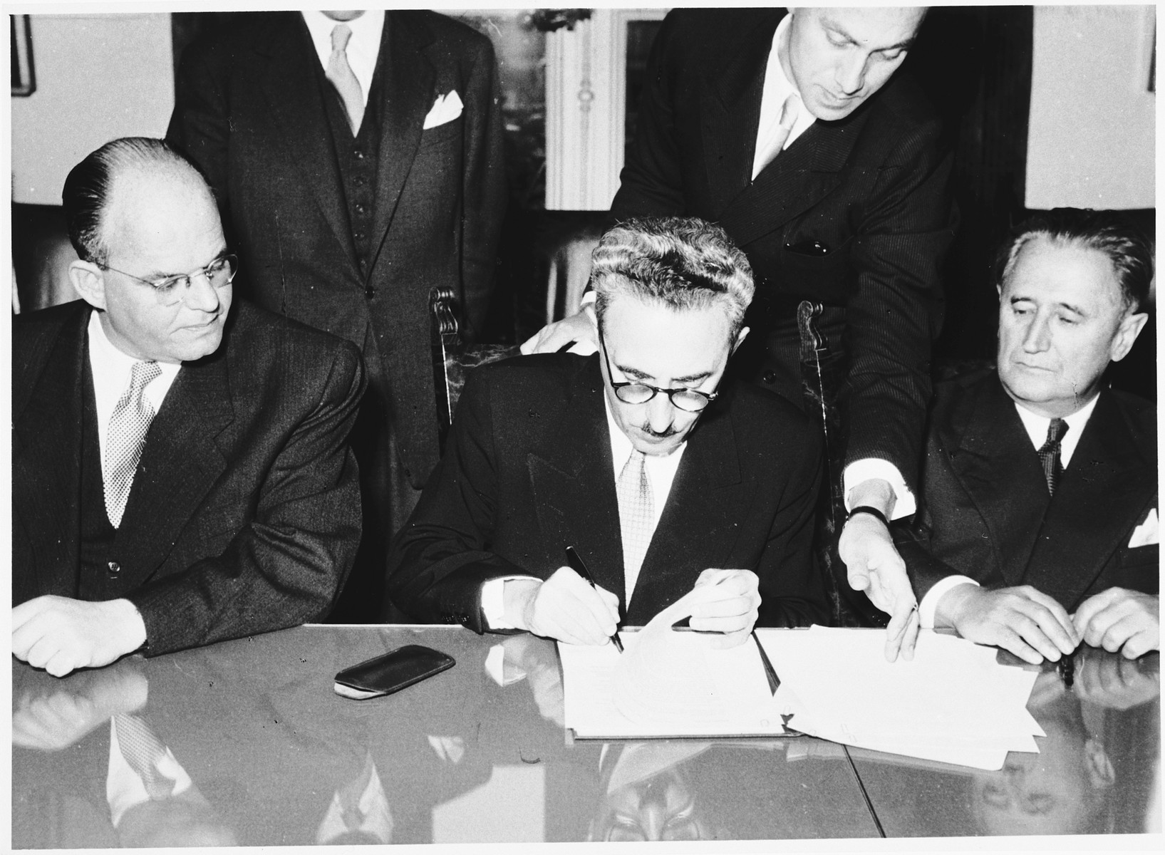 Israeli Foreign Minister Moshe Sharett signing the Reparations Agreement between West Germany, Israel, and the Committee on Jewish Material Claims.  Pictured seated from left to right are Giora Josephtal, Moshe Sharett and Nahum Goldmann.