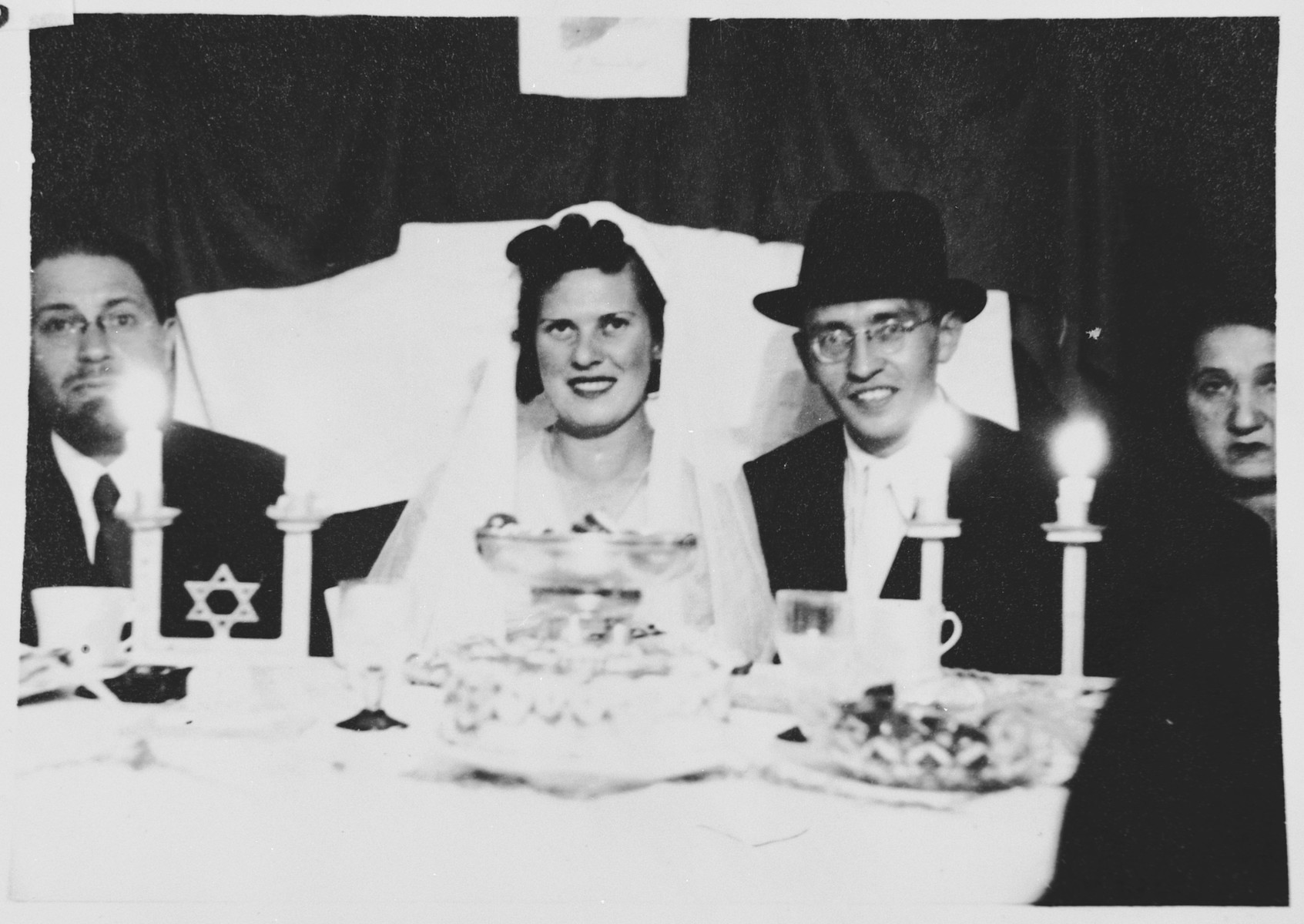 Two internees celebrate their wedding in the Ferramonti camp in a lunchtime ceremony performed by Rabbi Riccardo Pacifici.  Rabbi Pacifici is seated on the far left.