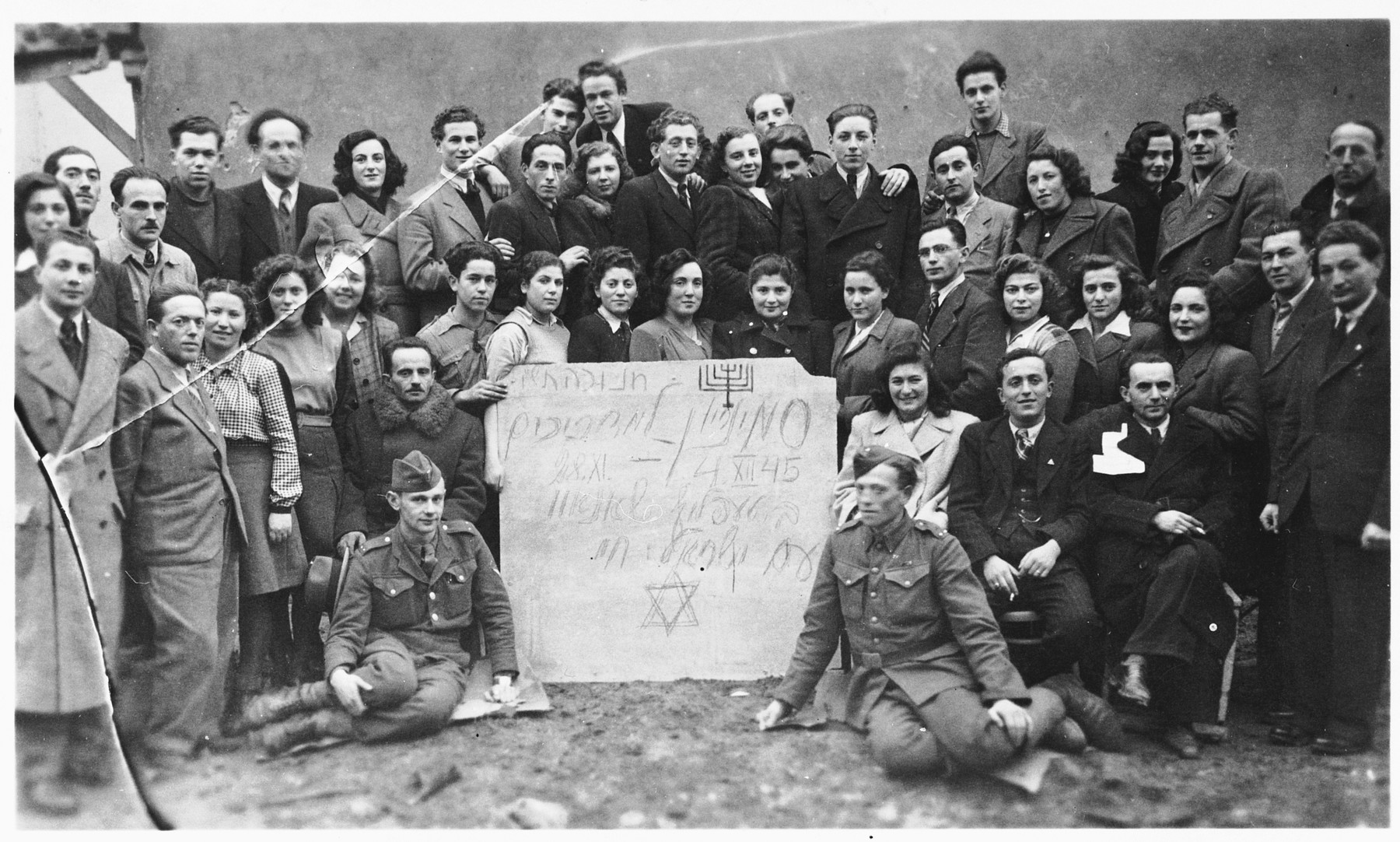 Group portrait of Jewish DP youth posing with a sign at a seminar of the Dror-Hehalutz Zionist youth movement in Czechoslovakia.  Among those pictured is Rahel Berger (second row from the front, fifth from the right).