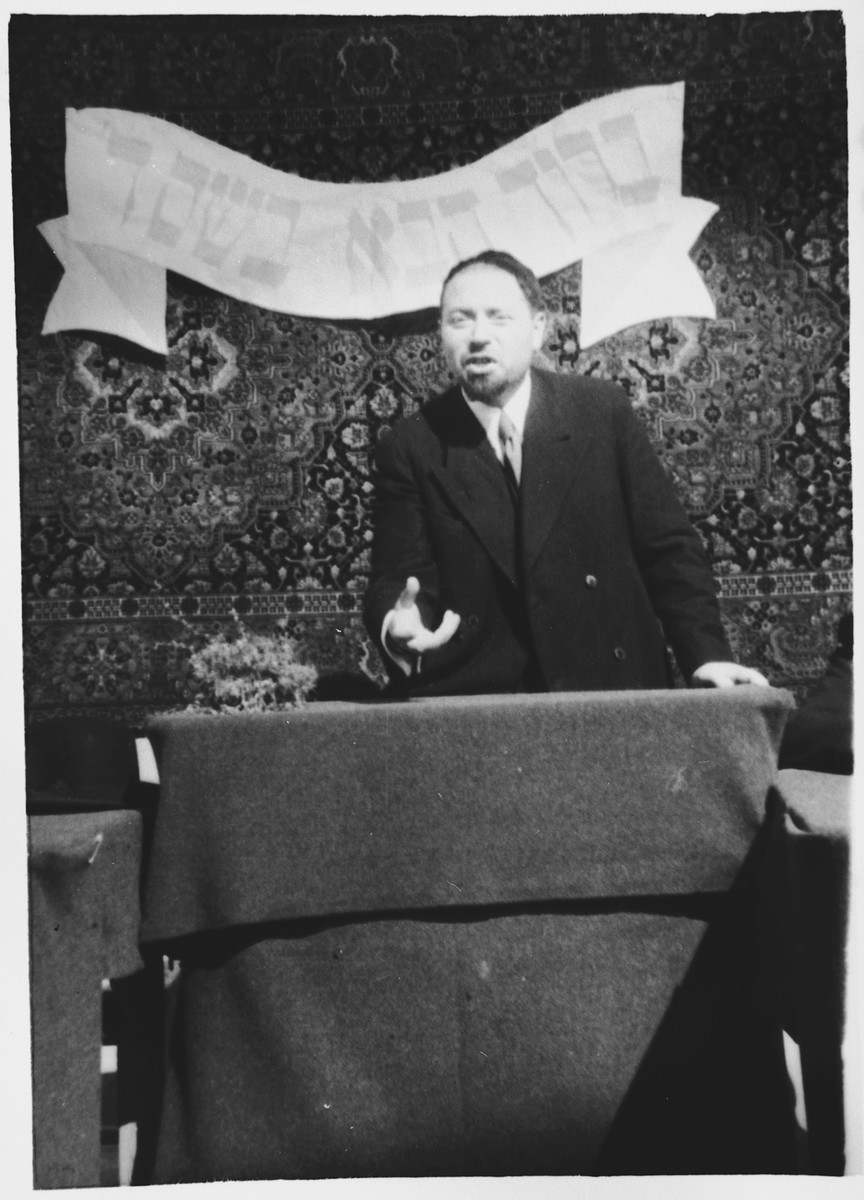 "Rabbi Riccardo Pacifici addresses the internees in the Ferramonti camp.  The banner behind him reads ""Blessed be your coming in the name of the Lord."""