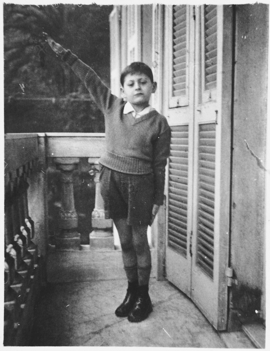 Emanuele Pacifici, a young Jewish boy makes the Fascist salute on the balcony of his house on Via Lanata.