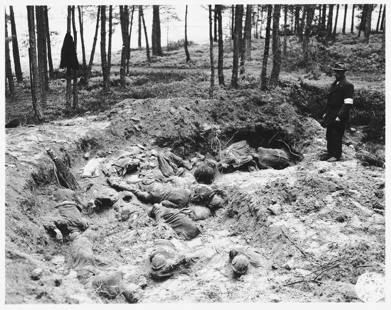 The local Burgomeister views the partially exhumed mass grave in Stamsried, Germany.  (Photograph taken by the 166th Signal Corps Company.)