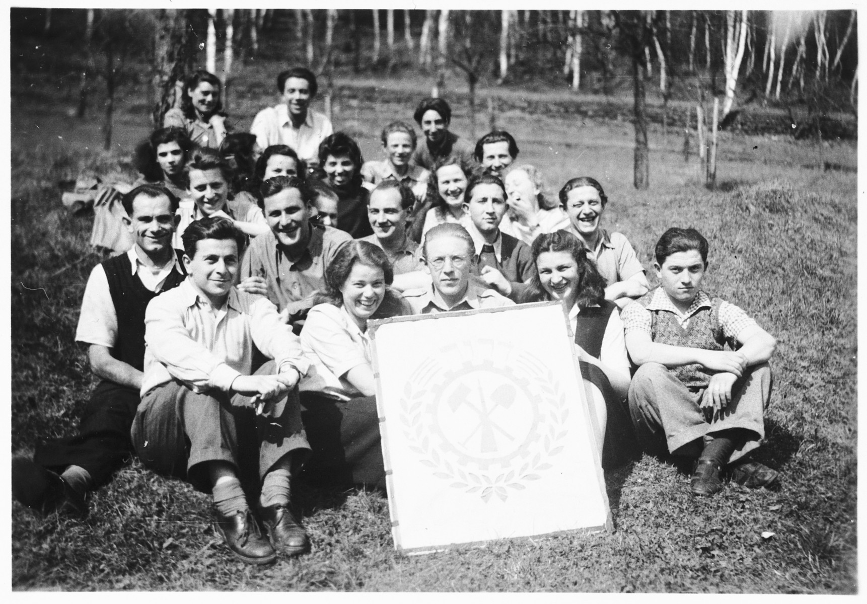 Group portrait of Jewish DPs of the Dror Hehalutz Zionist youth movement posing with a sign while on an outing in Czechoslovakia.