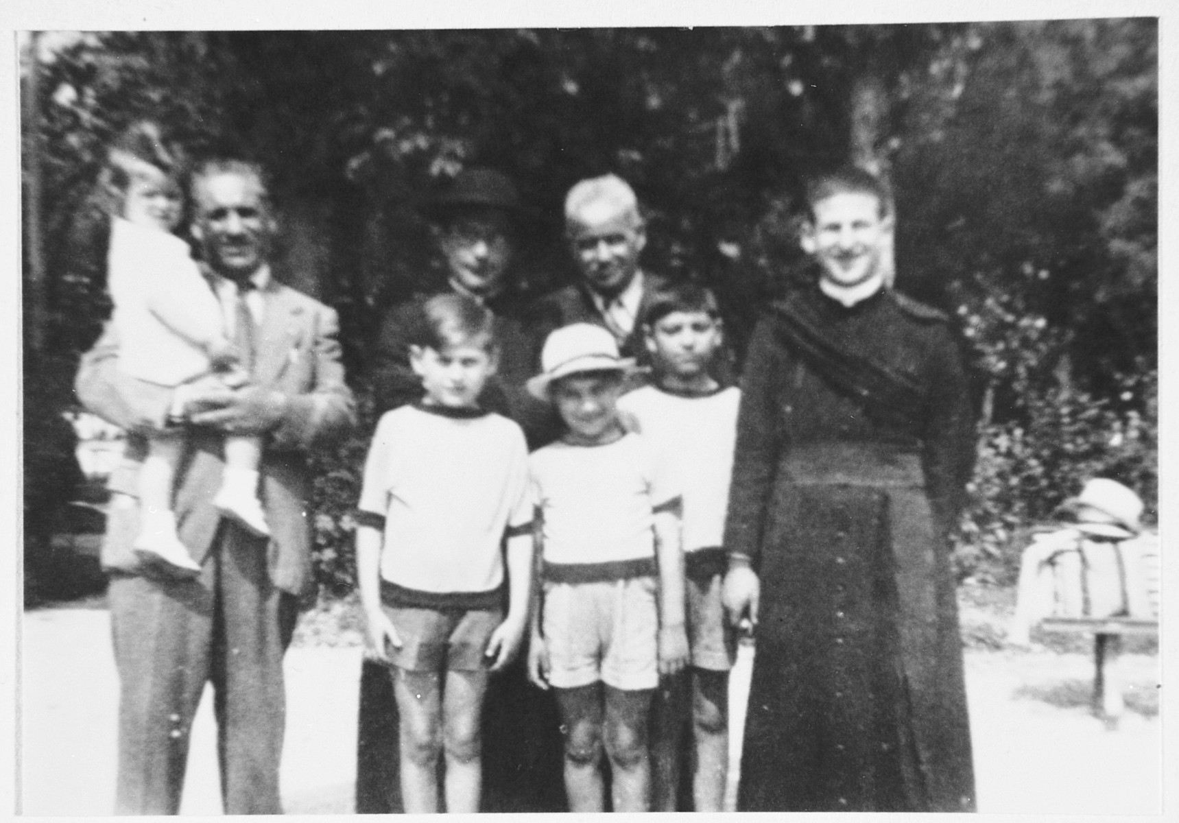 A Jewish family poses with a priest from the parish that hid them a few years later.  From left to right are Nathan Orvieto in the arms of his father, Enrico Orvieto (donor's uncle), Emanuele Pacifici, Guiliano Orvieto, Gualtiero Orvieto, and the priest whose name is unknown.  Behind them is Don Gaetano Tantalo and Mario Pacifici (the donor's paternal grandfather).  Don Gaetano Tantalo hid all nine members of the Ovieto family for approximately nine months.  He passed away a few months after the end of the war but in 1978 was recognized as Righteous Among the Nations.