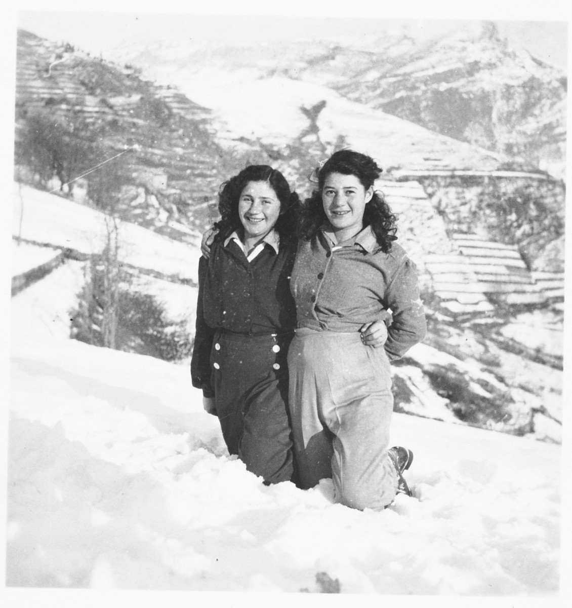 Two teenage girls pose together in the snow outside the Selvino children's home.  The Italian Alps can be seen in the background.