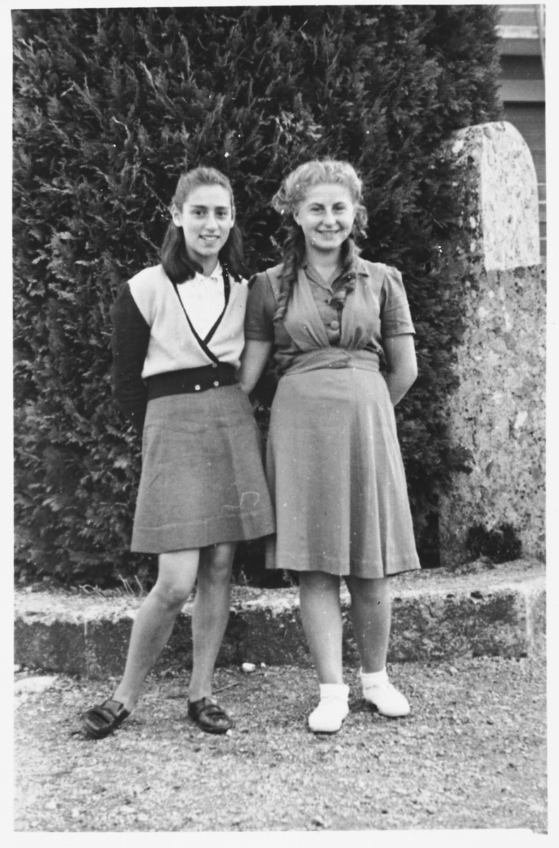 Two teenage girls pose together on the grounds of the Selvino children's home.  Ruth Rotenburg is on the left.  On the right is Chana Scheiner.
