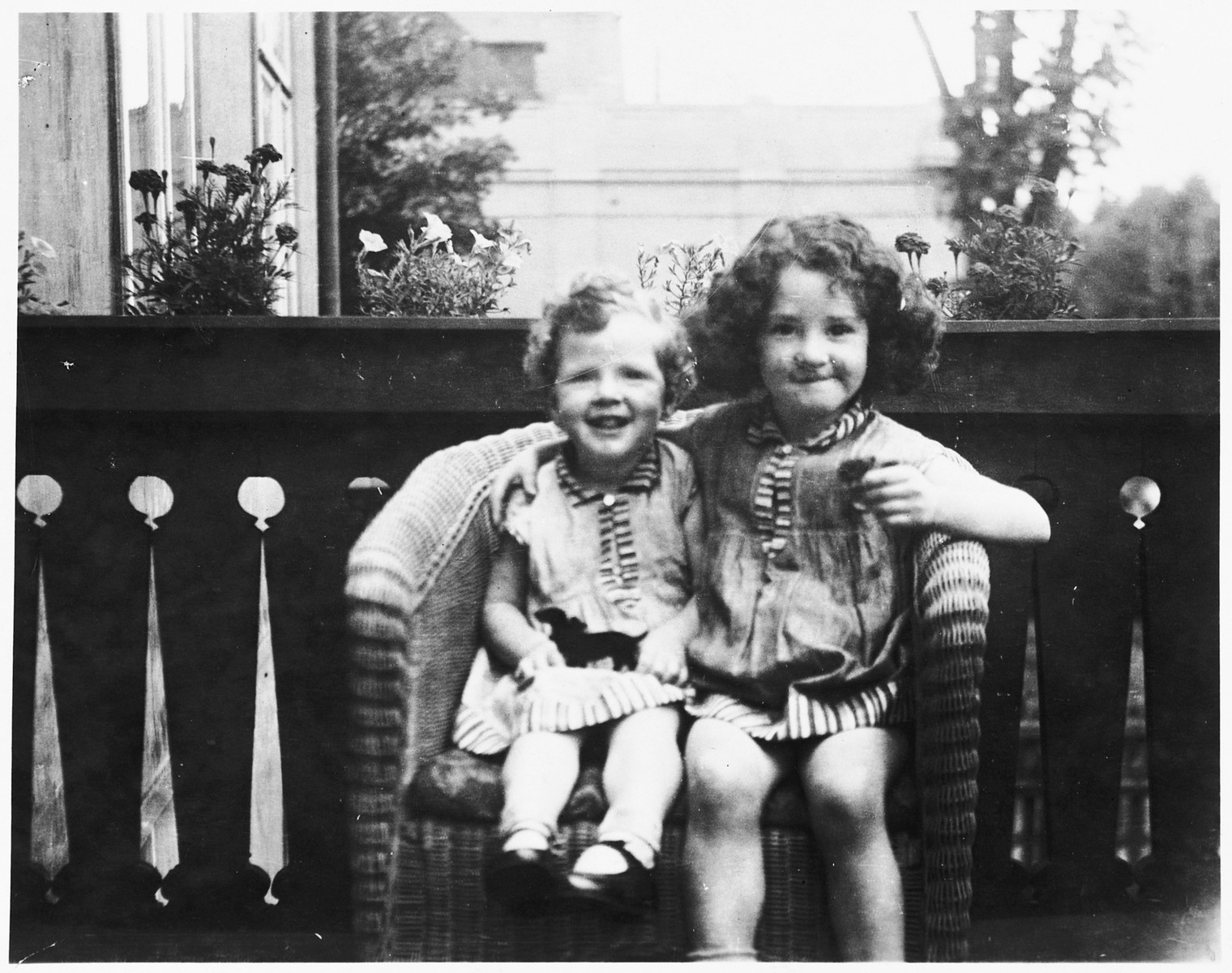 Shulamit and Gitta Posner share a wicker chair on the porch of their home in Kiel, Germany.