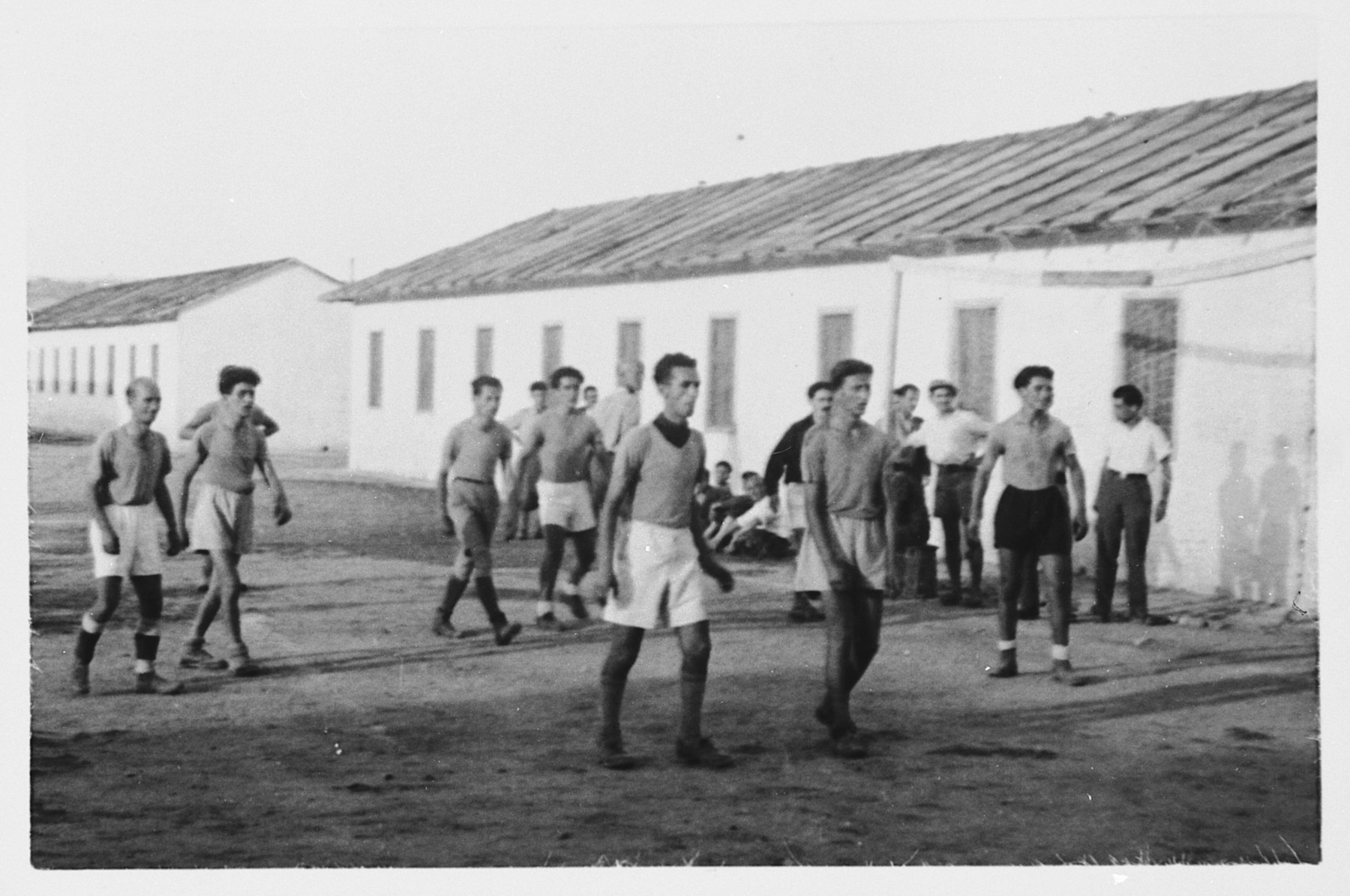 Members of an internee soccer team walk through the Ferramonti internment camp.  This photograph was taken during a visit by Rabbi Pacifici to the internees.