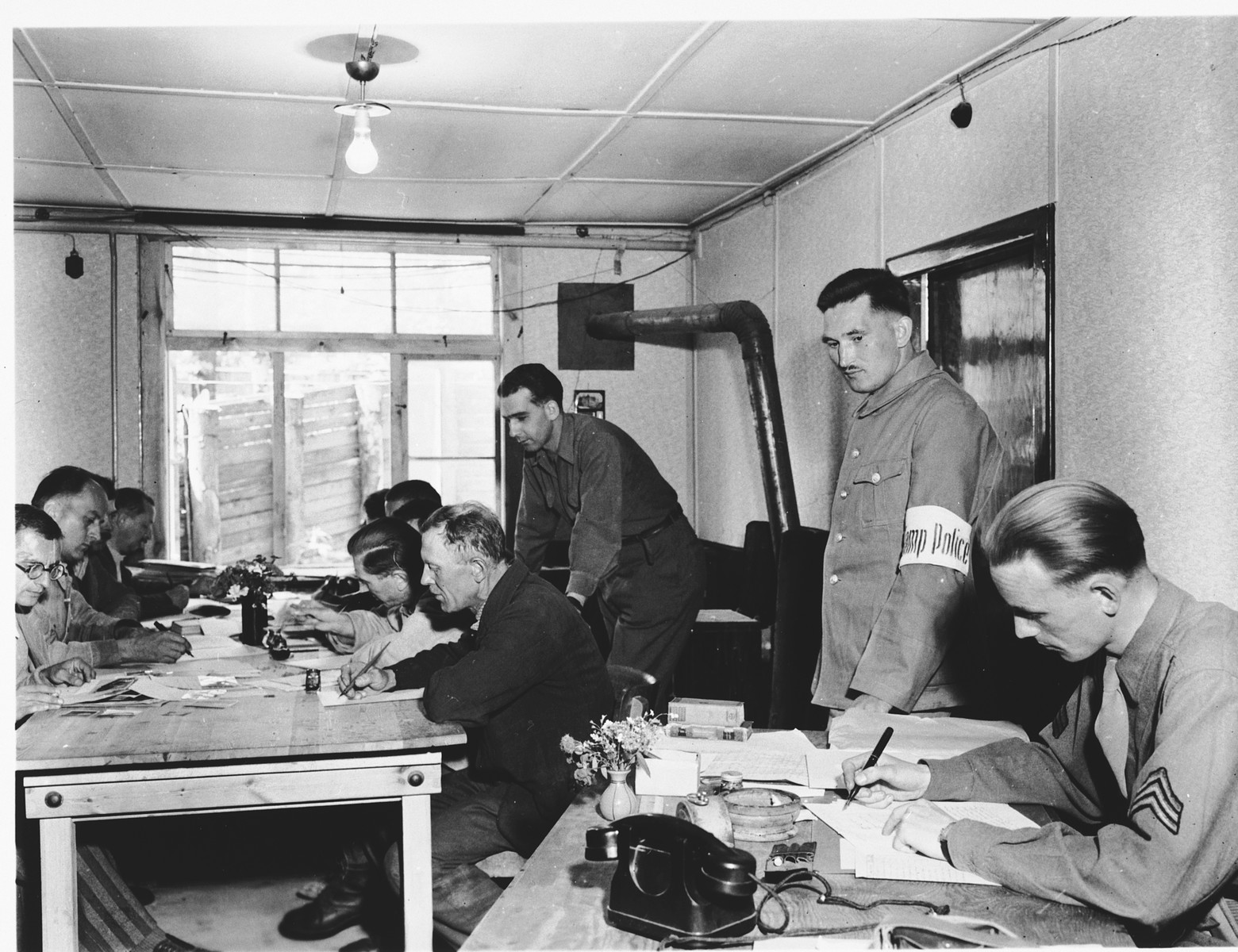 Men at work in the war crimes commission office established in Dachau.  On a right is a Dutch translator translating documents.