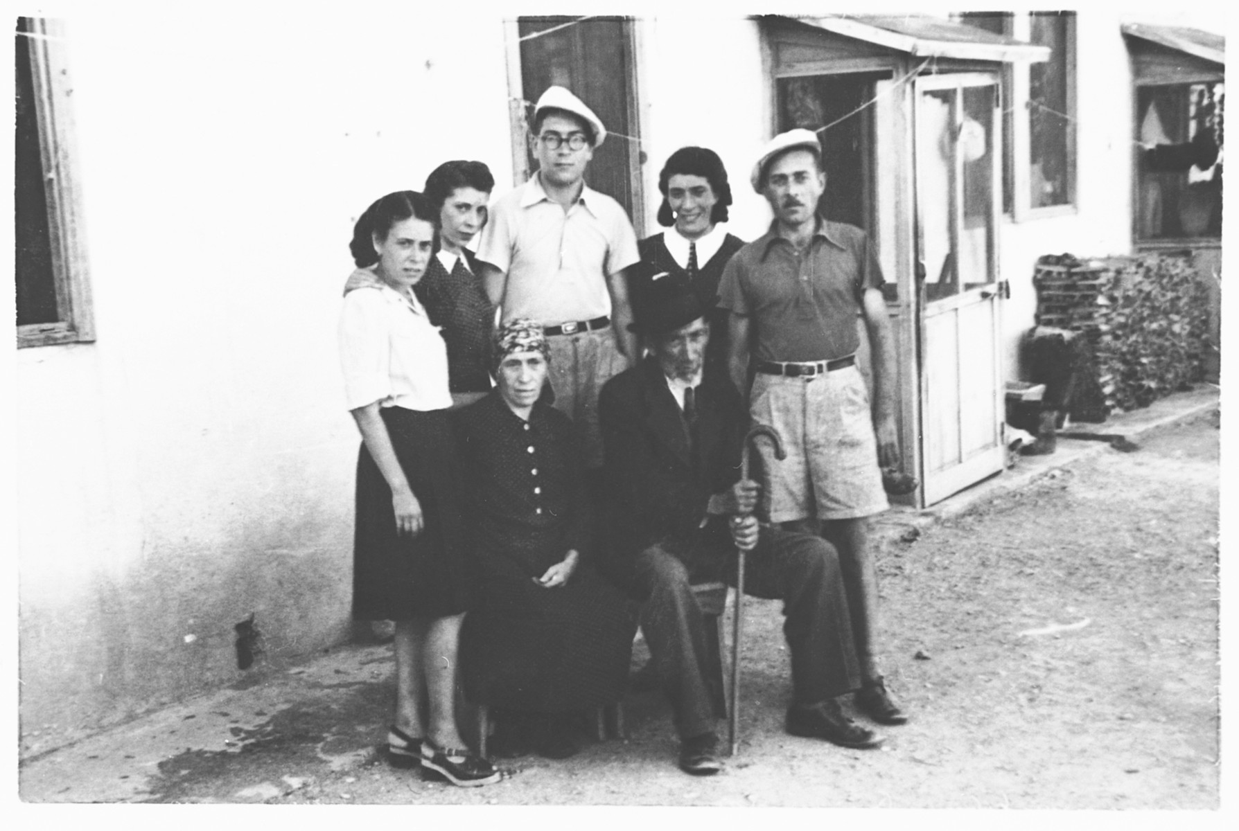 Group portrait of the Ermanno Stern family, internees in the Ferramonti camp.  This photograph was taken during a visit by Rabbi Riccardo Pacifici.