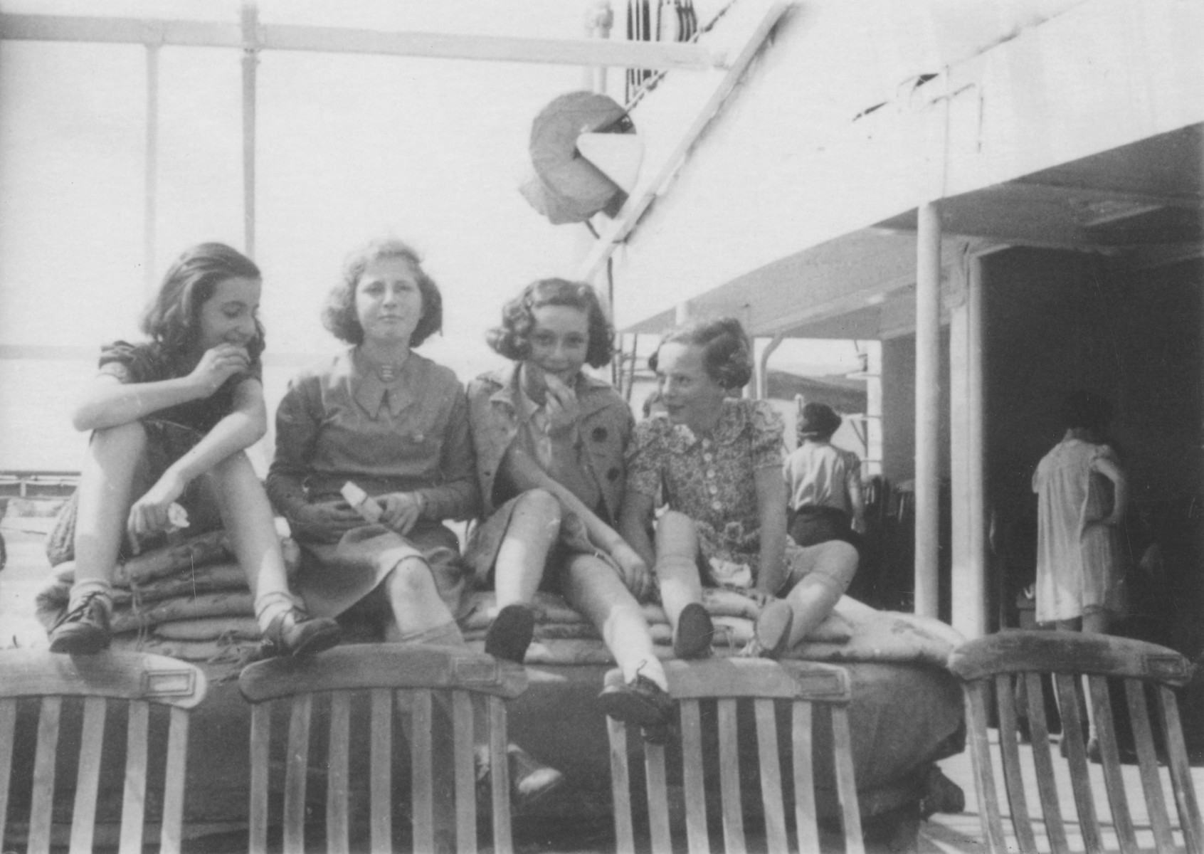 Four girls share a snack on the deck of the MS St. Louis.