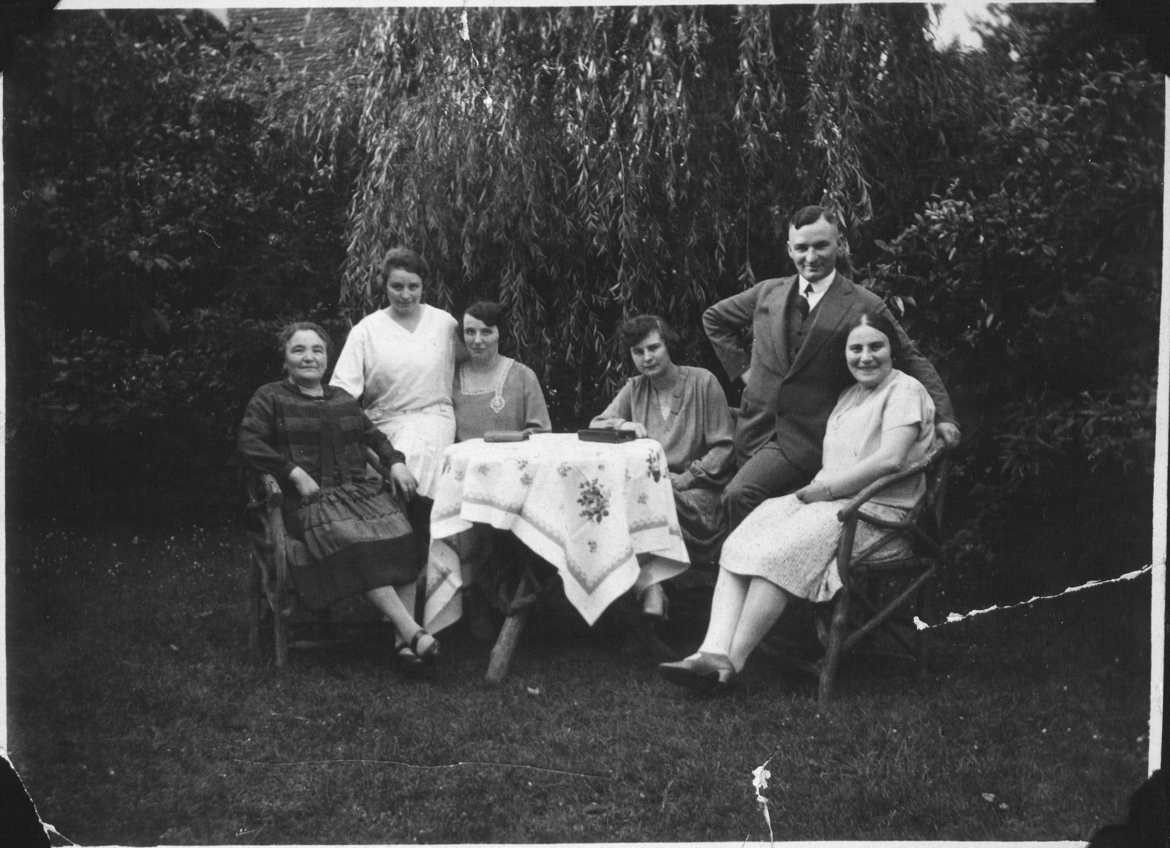 Members of the Meyer family pose outside in the yard seated around a table in Moenchengladbach, Germany.  Pictured in the back is Sol Meyer.