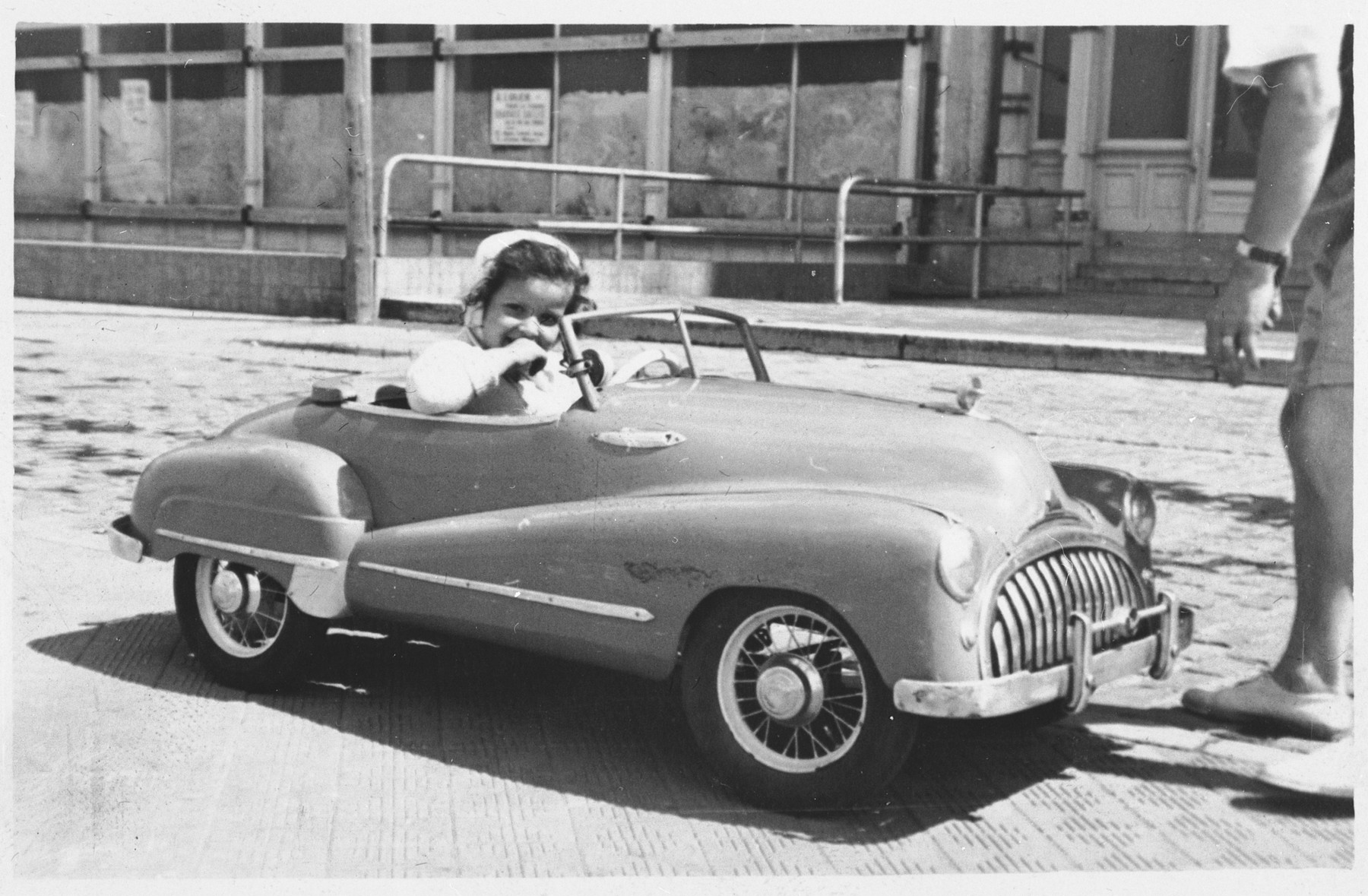 Marie-Claire goes for a ride in a toy car while staying with the Hickett family.
