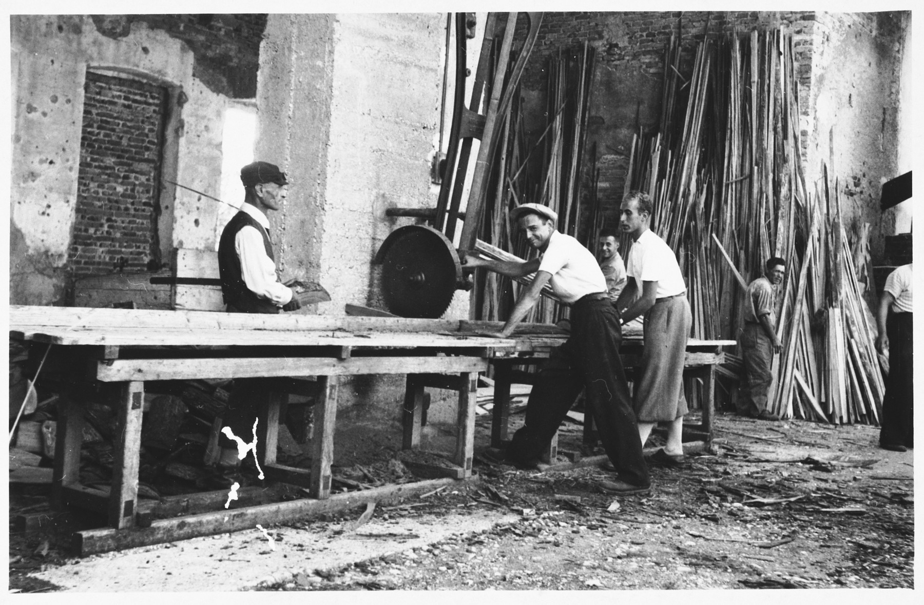 A group of young Jewish men at forced labor in a lumber mill in Gorizia, Italy.  Among those pictured are Marcello Morpugo (right, at the table) and Giacomo Donati (second from right at the table).  Giacomo was later killed during the war as a partisan.