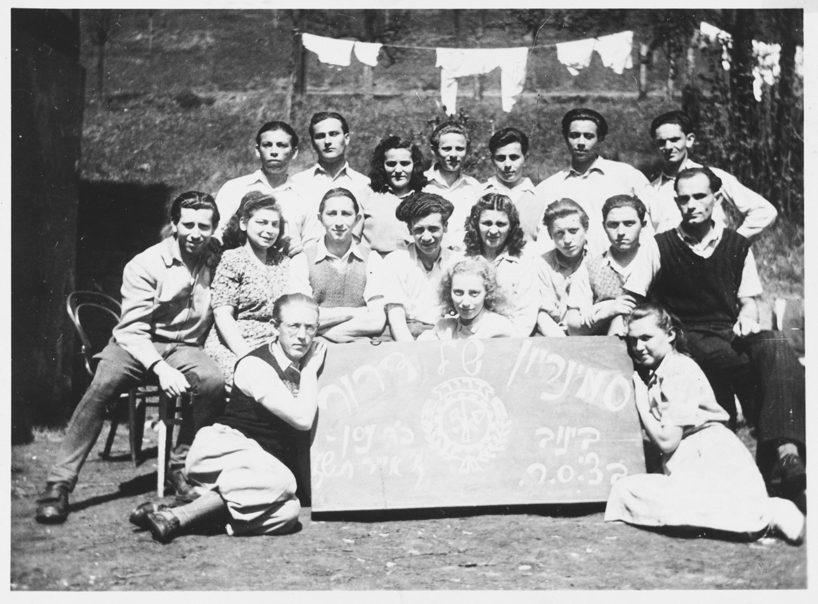 Group portrait of Jewish DP youth posing with a sign at a seminar of the Dror-Hehalutz Zionist youth movement in Czechoslovakia.