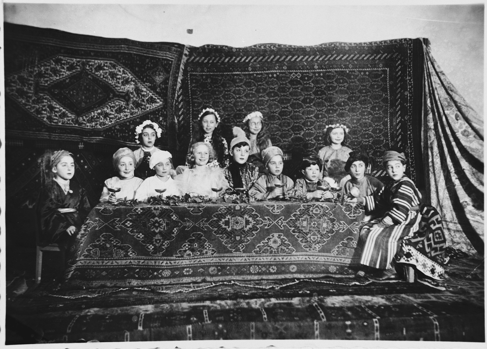 Children in a Hebrew school in Genoa perform a Purim play.  Emanuele Pacifici is seated at the left in the white beret.