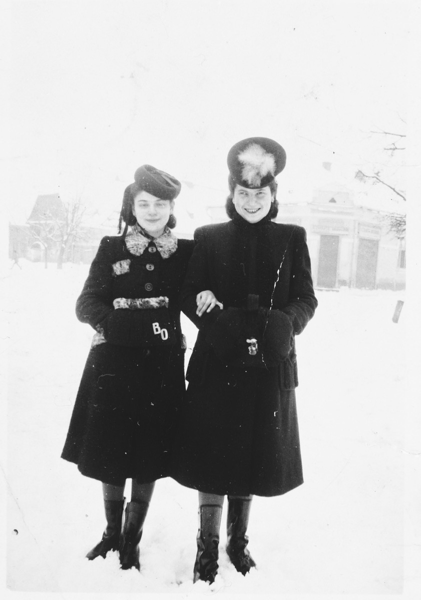 Two young Jewish women pose in winter coats and boots on a snowy street in Tacovo.