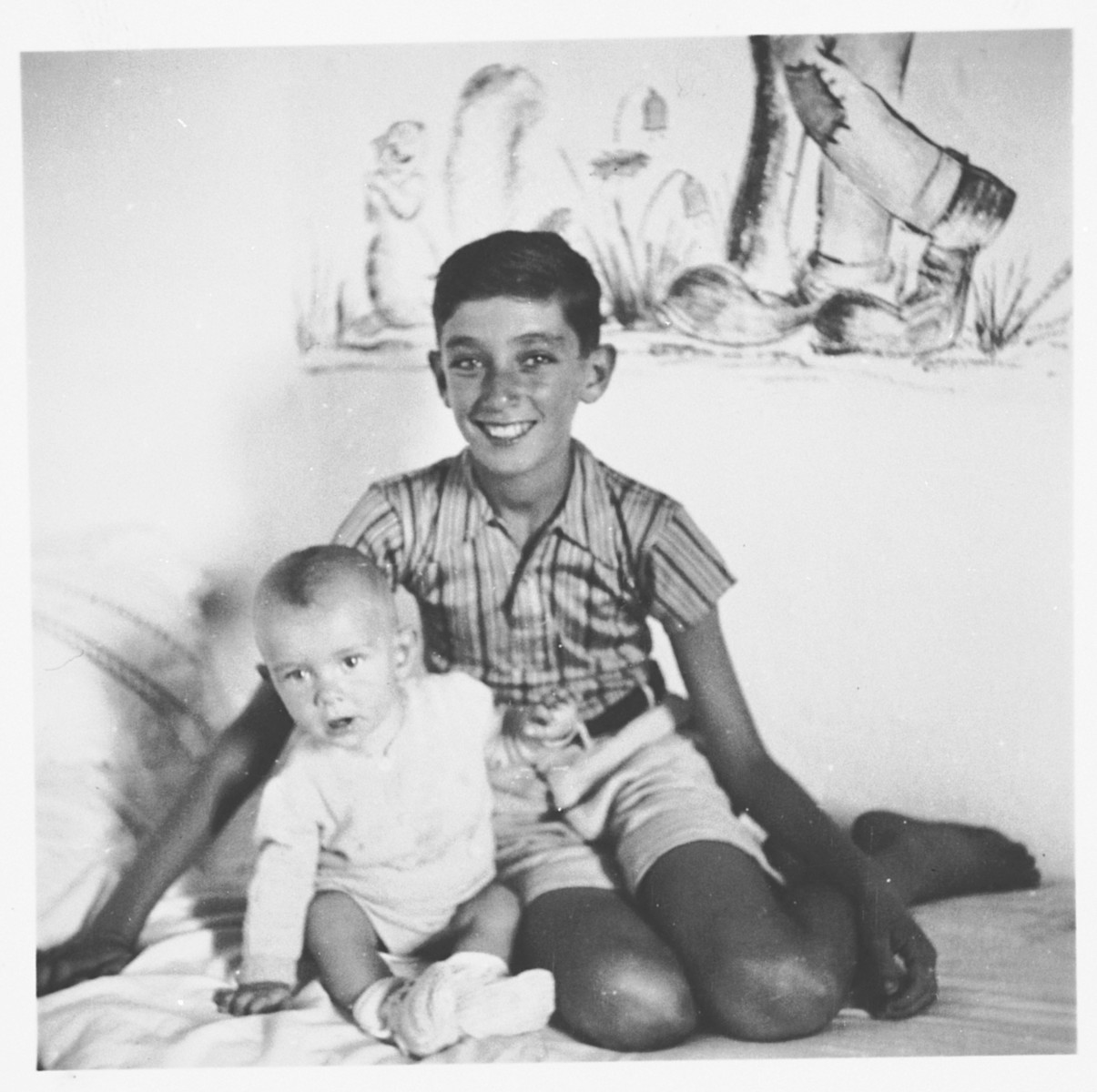 Two children pose on a bed in the Ferramonti internment camp.  The baby's name was Walter.  This photograph was taken during a visit to the camp by Rabbi Pacifici.