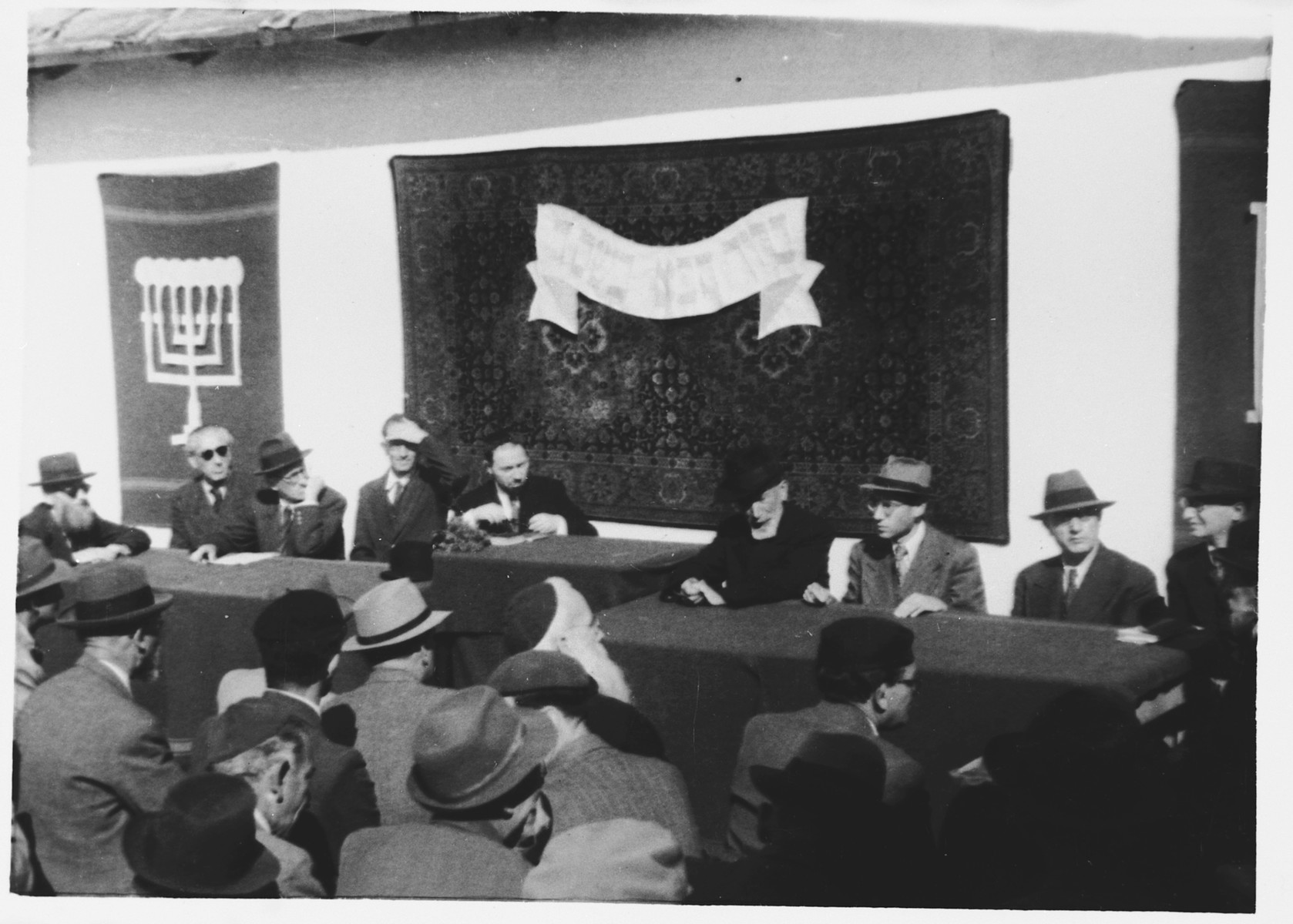 """Internees gather for a meeting in the Ferramonti camp to determine work assignments.  This photograph was taken during a visit to the camp by Rabbi Pacifici.  Rabbi Pacifici is seated in the center.  The banner behind him reads """"Blessed be your coming in the name of the Lord."""""""