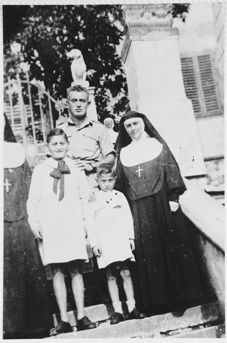 Shortly after liberation, three Jewish children pose with the Mother Superior of a convent where they had hid during the war.  From left to right are Emanuele Pacifici, his brother Raffaele, and Sister Benedetta Vespignani.  Behind them is Moshe Roskoun.