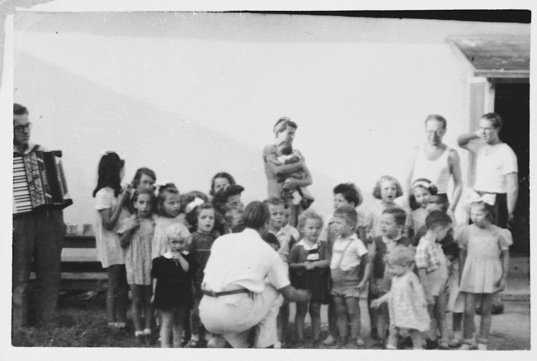 A man with an accordian accompanies a group of young children in song in the Ferramonti internment camp.  This photograph was taken during the first of three visit by Rabbi Riccardo Pacifici to the internees.  His last visit was in August 1943.