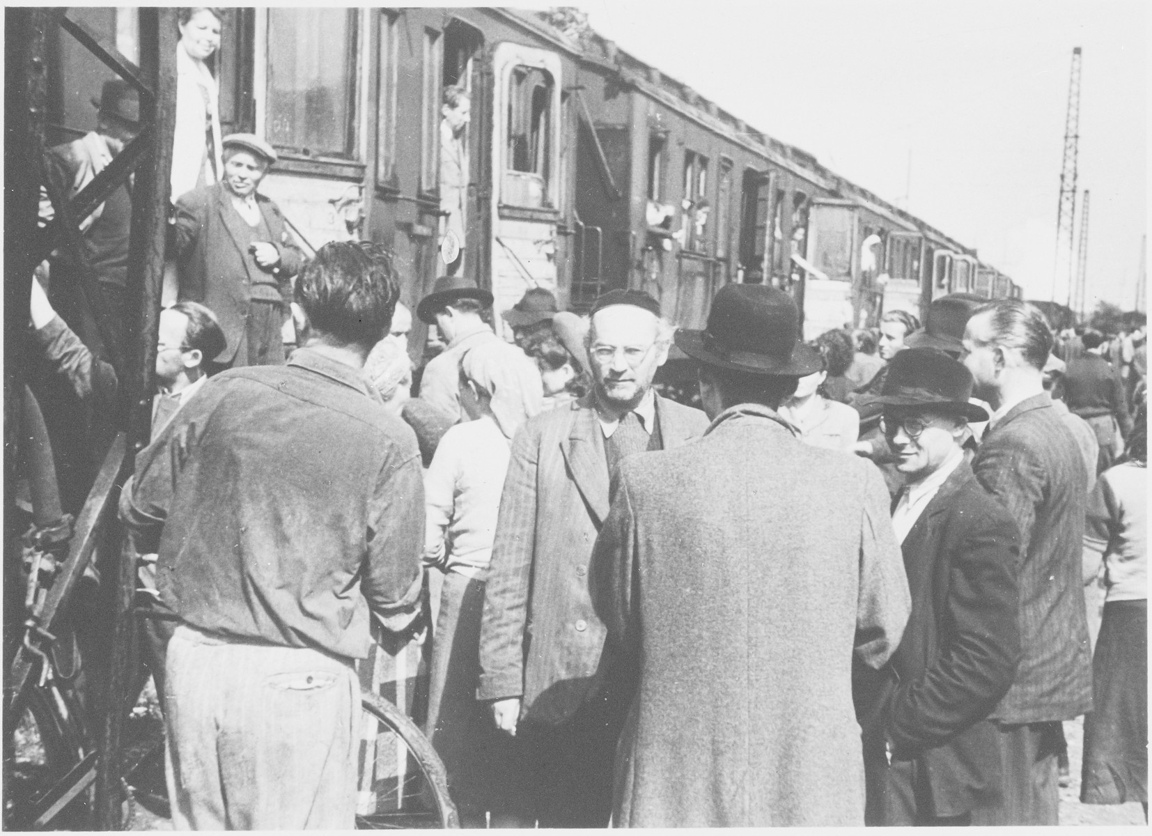 Jewish displaced persons board and exit a train in a busy station in Germany.