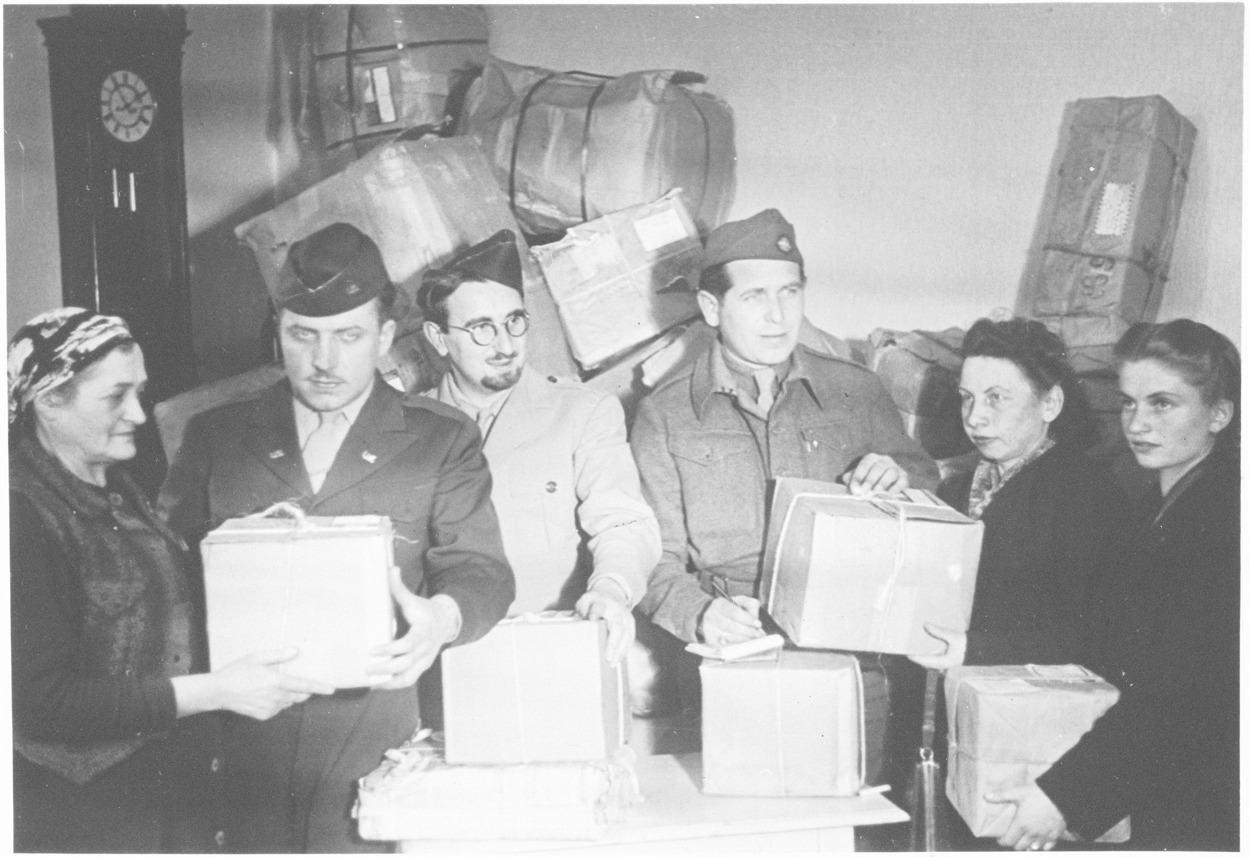 Rabbis Nathan Baruch (second from the left) and Aviezer Burstein (third from the left) deliver Passover supplies to Jewish displaced persons.