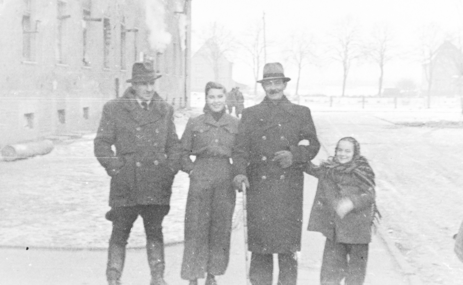 """A group of survivors stand in the cold at the Wetzlar diplaced persons camp.  A young girl named Edith, wrapped in a scarf, stands on the right.  The original caption reads, """"1947."""""""