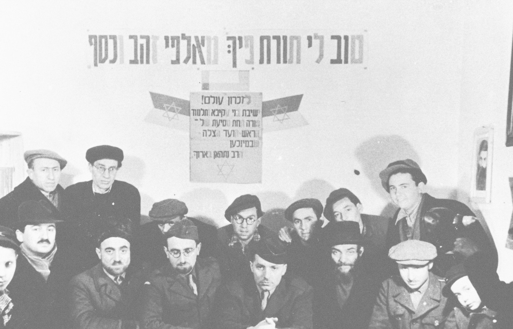"""Group portrait of participants in a meeting of the Mizrachi religious Zionists in Aschau.  Rabbi Nathan Baruch is pictured in the center and Rabbi Aviezer Burstein is pictured to his left.  The sign on the back reads """"The words of Torah from your mouth are more precious to me than thousands of gold and silver""""."""