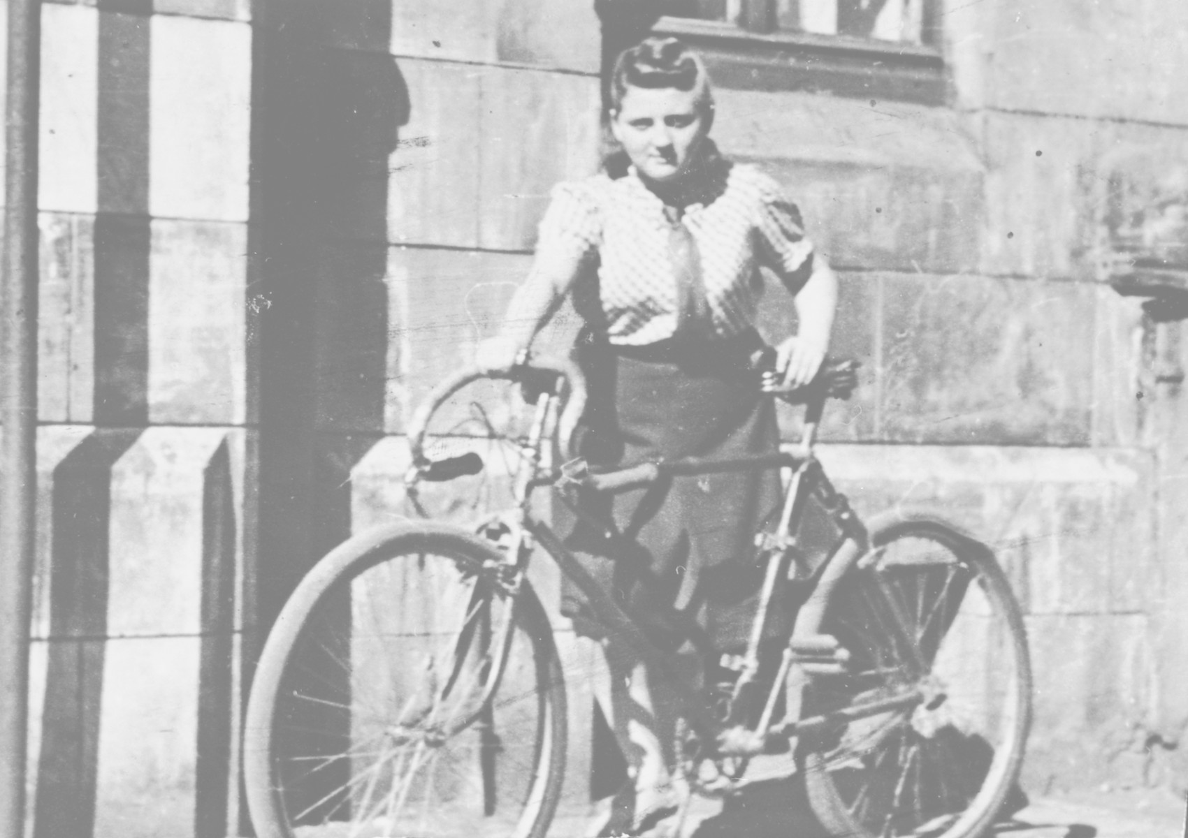Frymka Russinek stands with her bicycle on the street after the war.