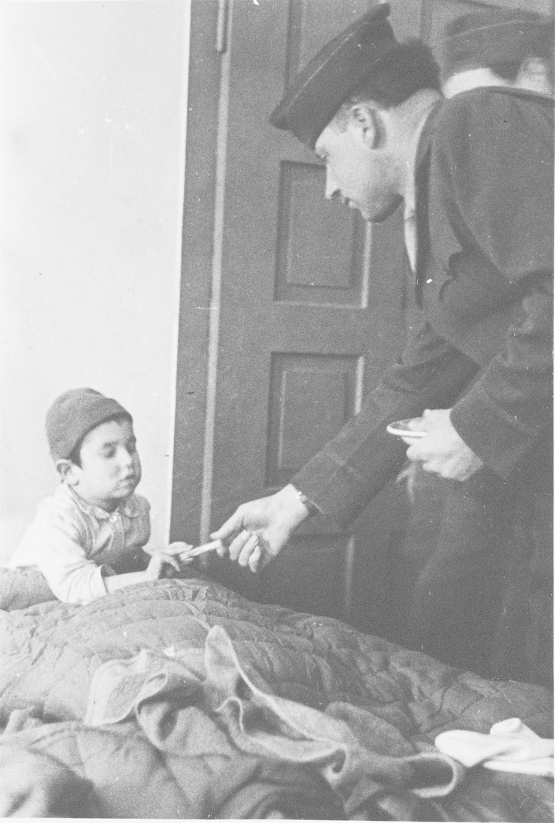 Rabbi Nathan Baruch visits a young child in bed in the Ulm displaced persons' camp.
