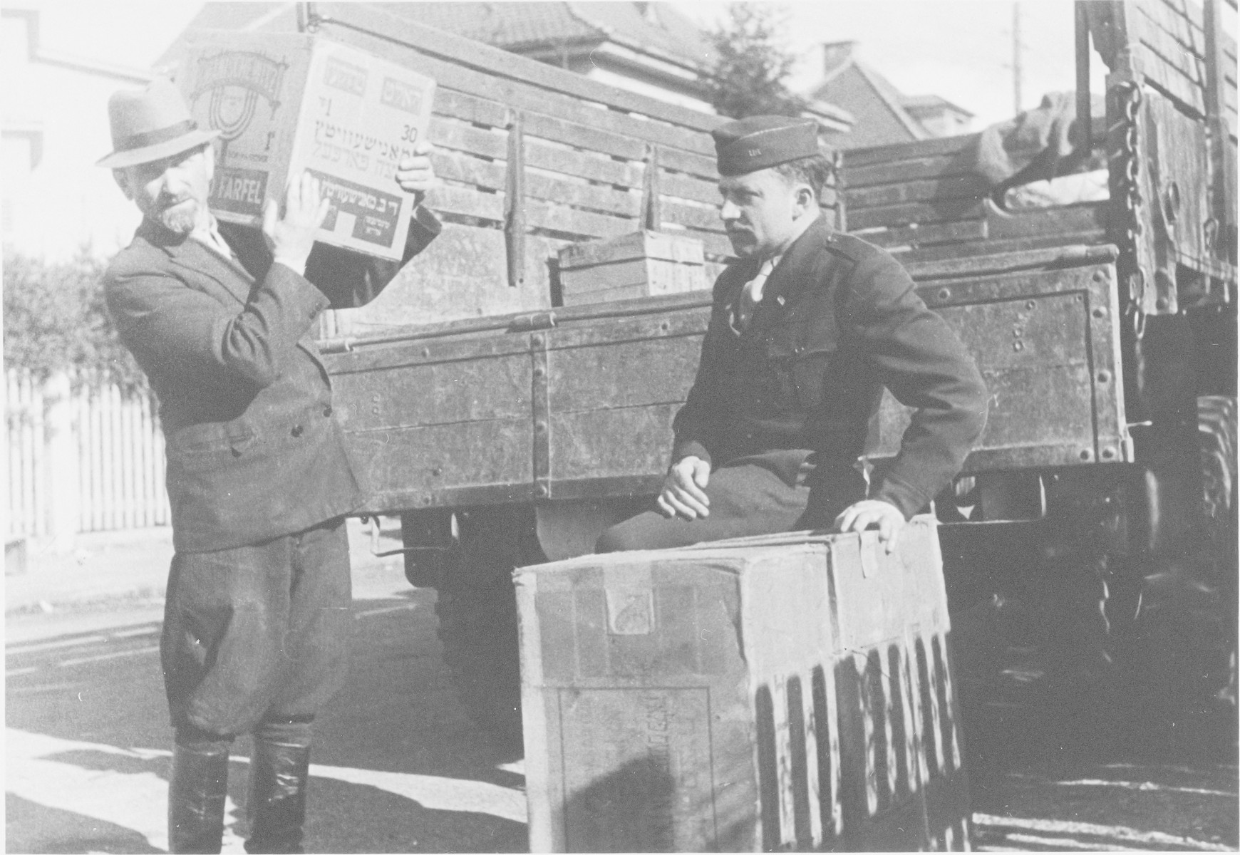 Rabbi Nathan Baruch oversees the unloading of Passover matza in an unidentified displaced persons' camp.