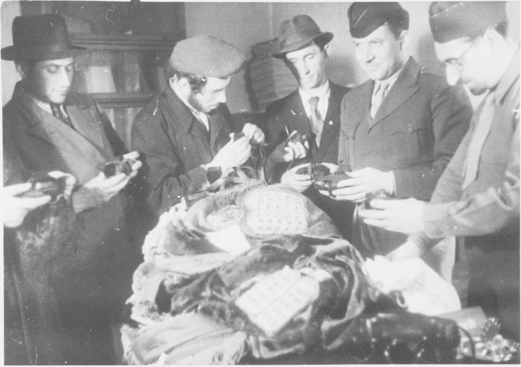 Rabbi Nathan Baruch, ,Rabbi Aviezer Burstein and a group of religious displaced persons sort through various religious articles.